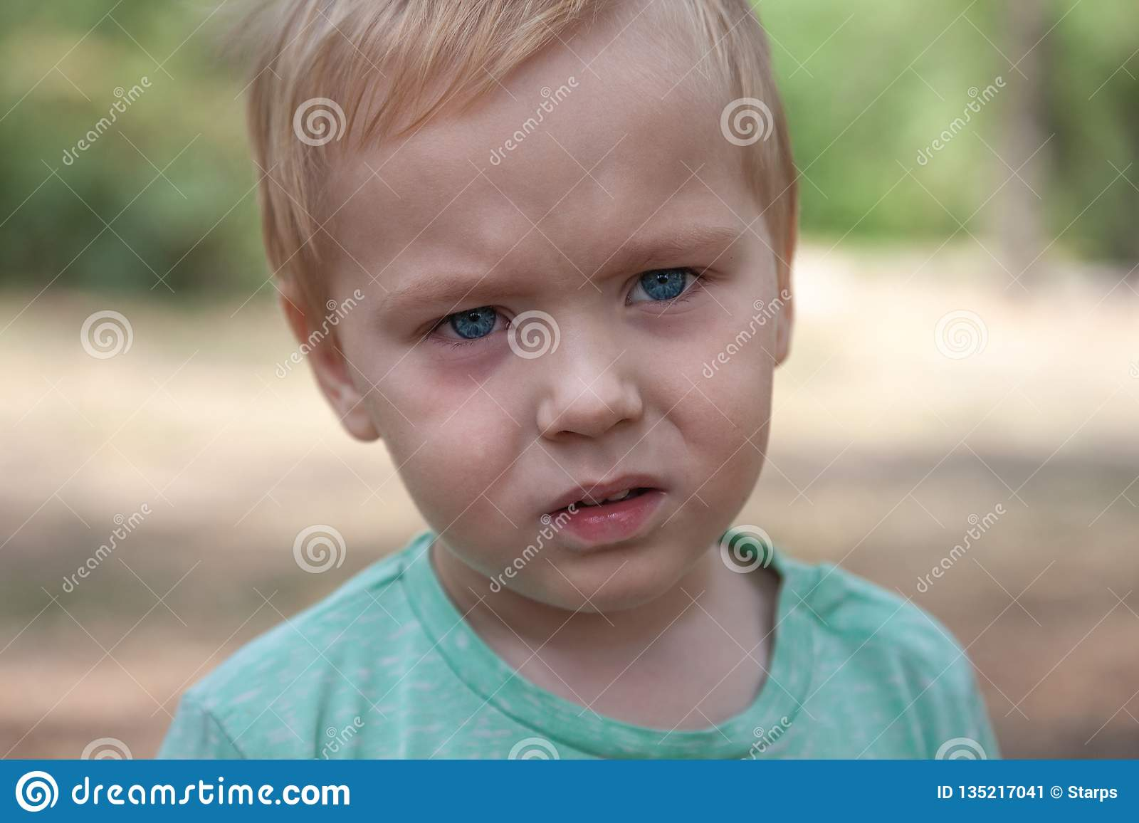 Retrato ascendente cercano del bebé caucásico lindo con la expresión seria en ojos azules