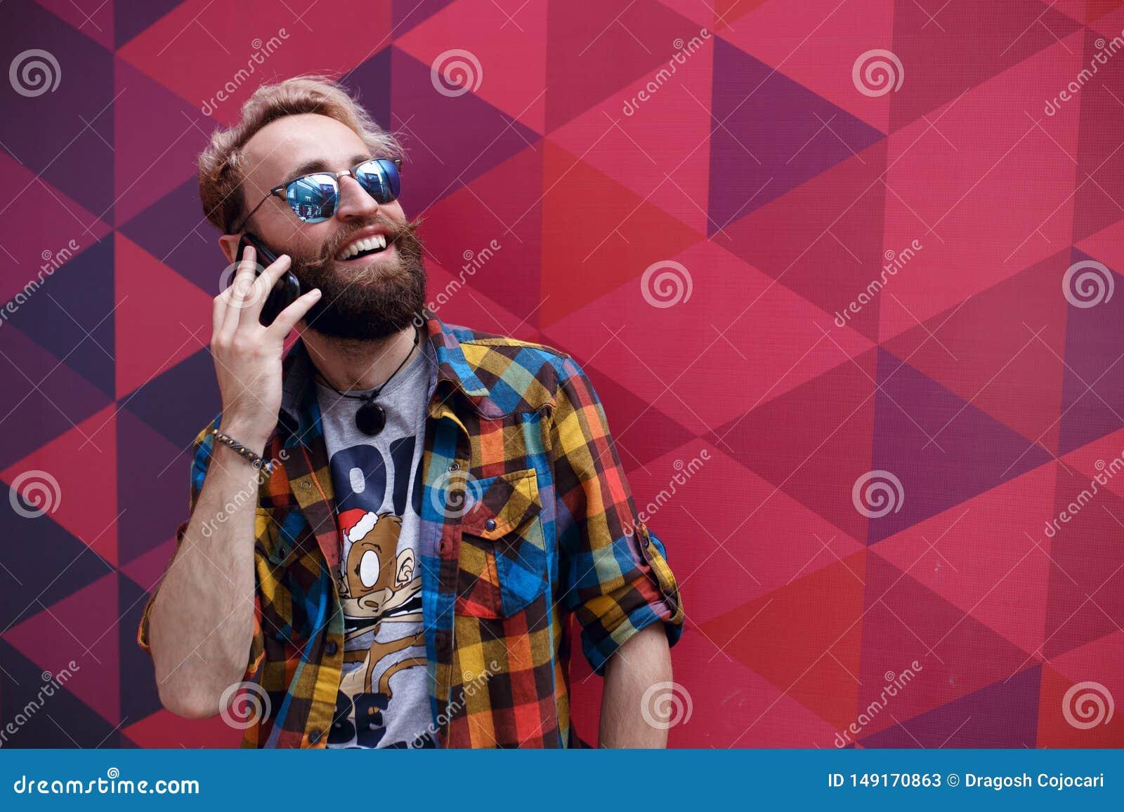 Retrato ascendente cercano del individuo maduro feliz que habla en el teléfono celular y que sonríe, aislado en un fondo colorido