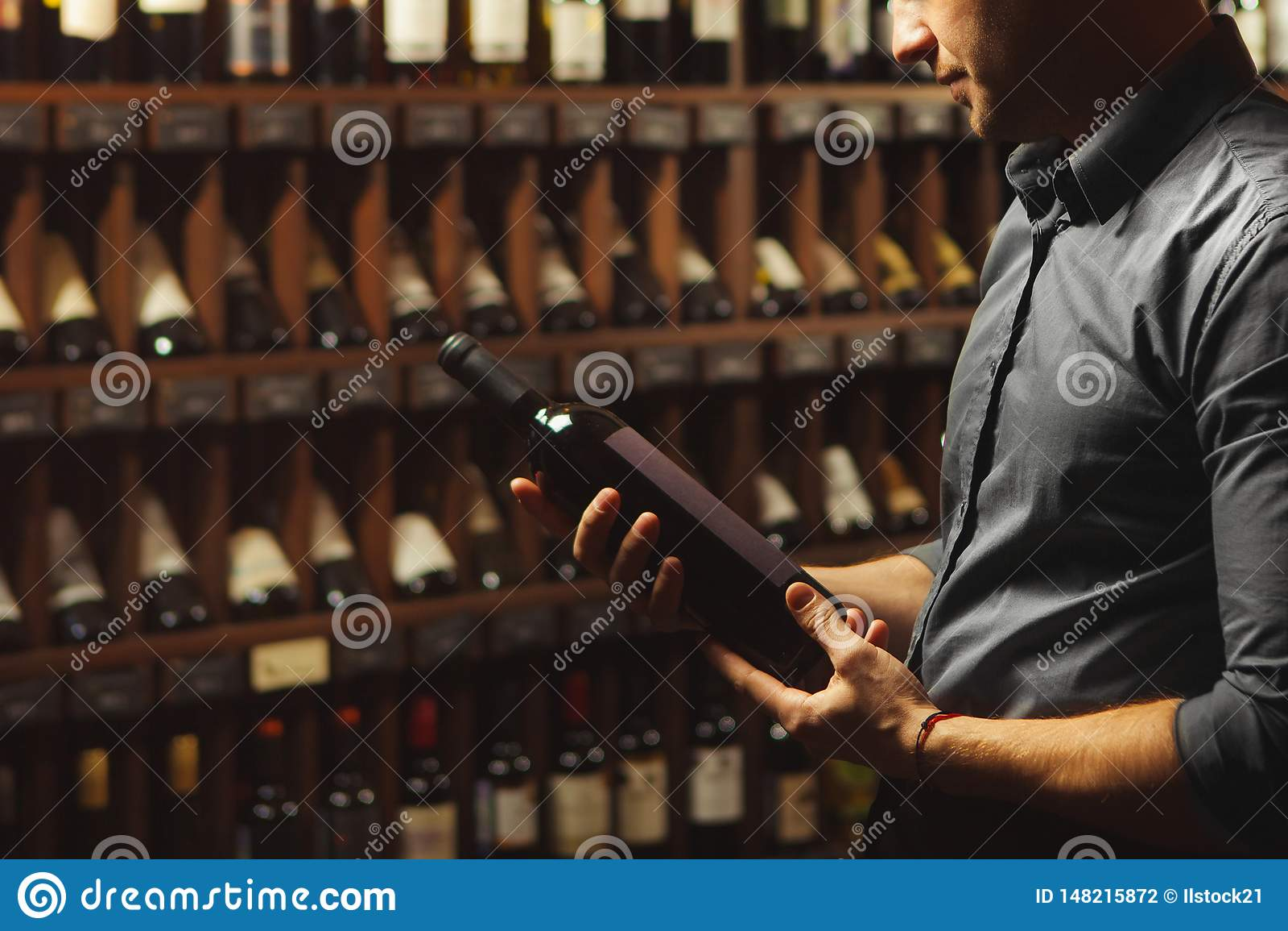 Retrato ascendente cercano del sommelier que sostiene la botella de vino en fondo de la bodega