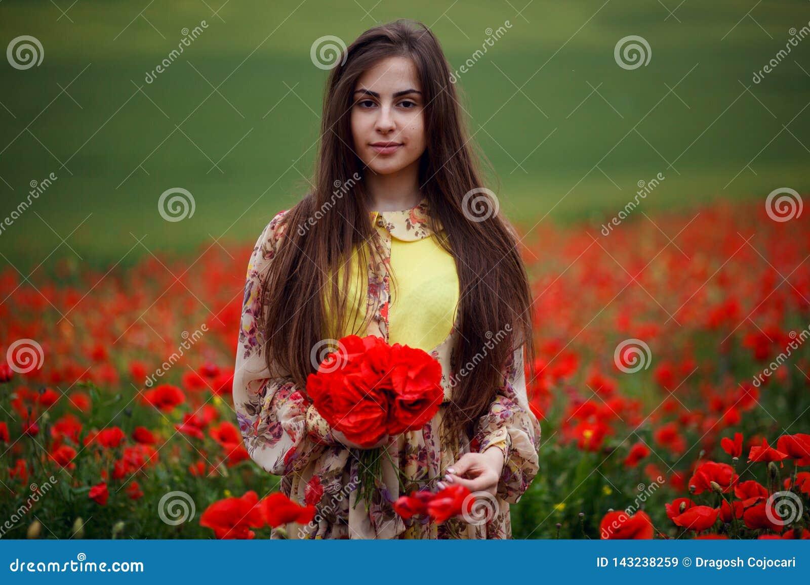 Retrato ascendente próximo da jovem mulher longa do cabelo com papoila da flor, terras arrendadas nas mãos um ramalhete do flores