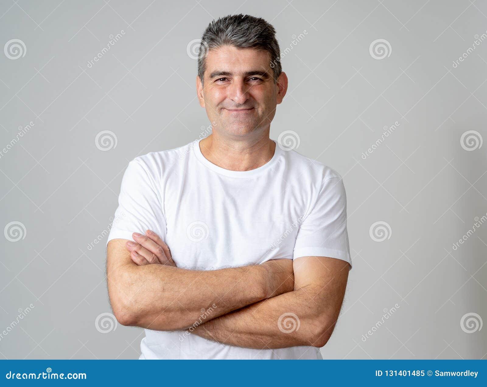 Retrato ascendente próximo de um homem envelhecido médio atrativo que tem o divertimento e que olha o sorriso alegre feliz e rir