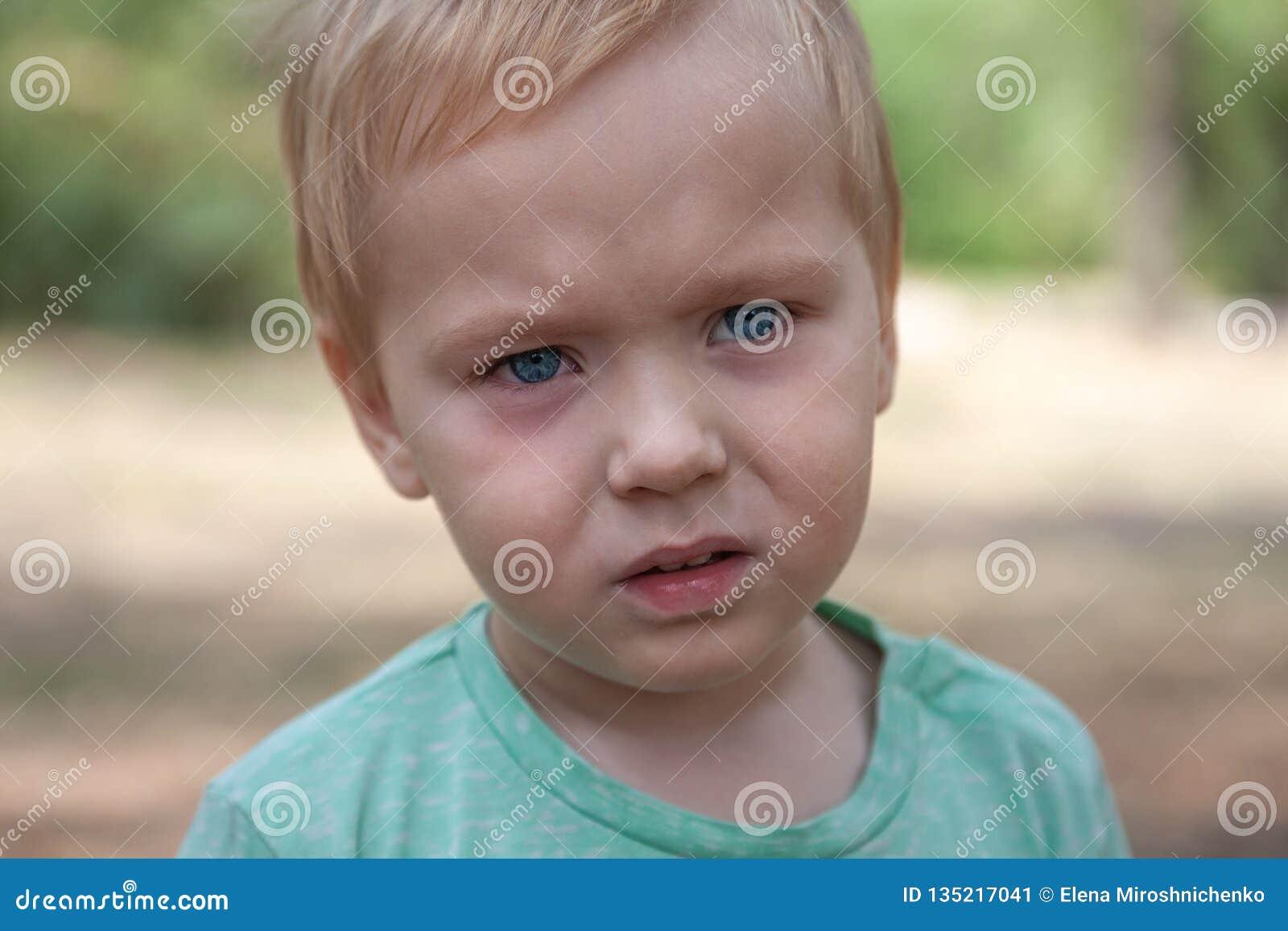 Retrato ascendente próximo do bebê caucasiano bonito com expressão séria nos olhos azuis
