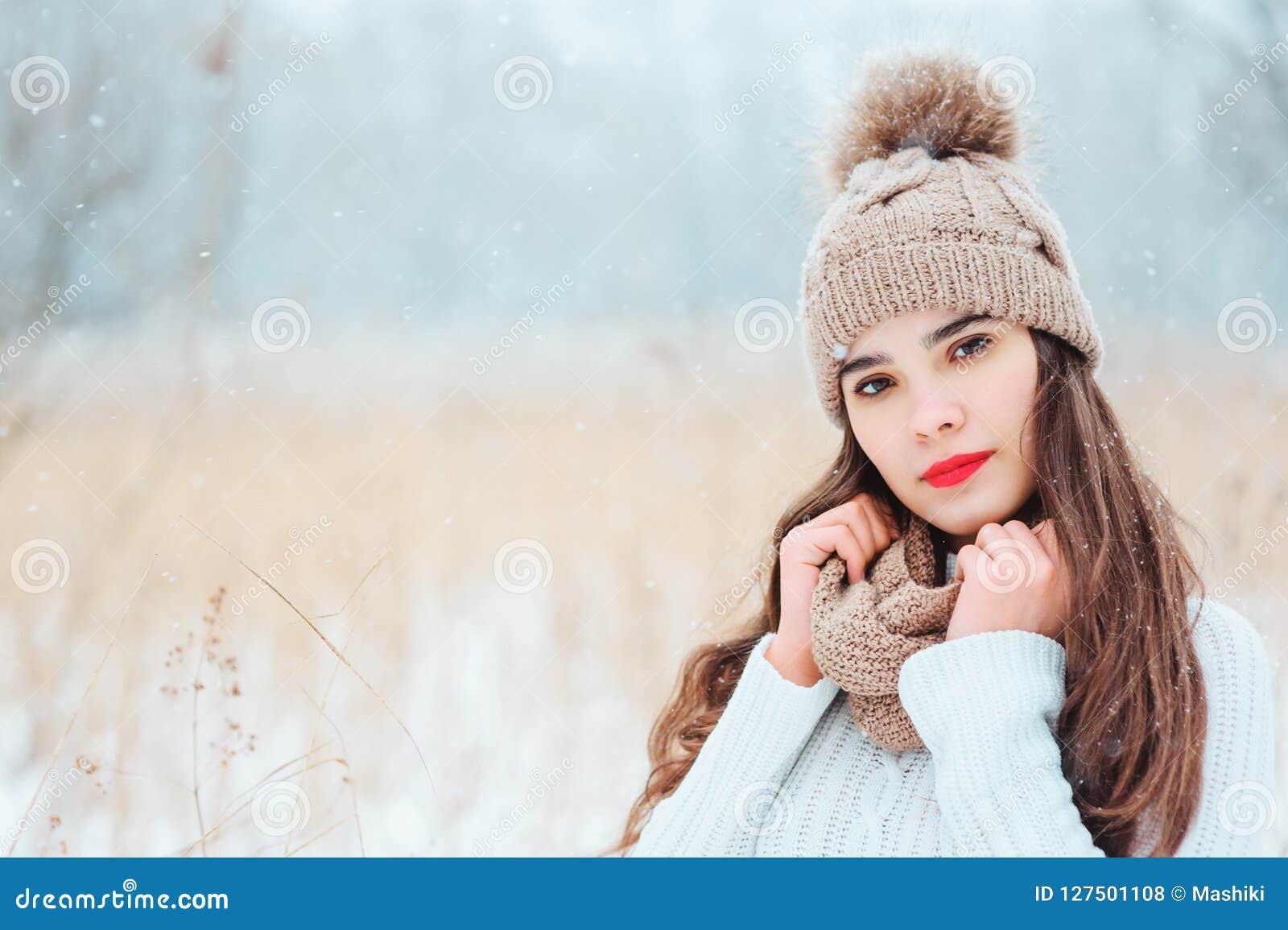 Retrato ascendente próximo do inverno da jovem mulher de sorriso bonita na queda de neve inferior exterior de passeio feita malha