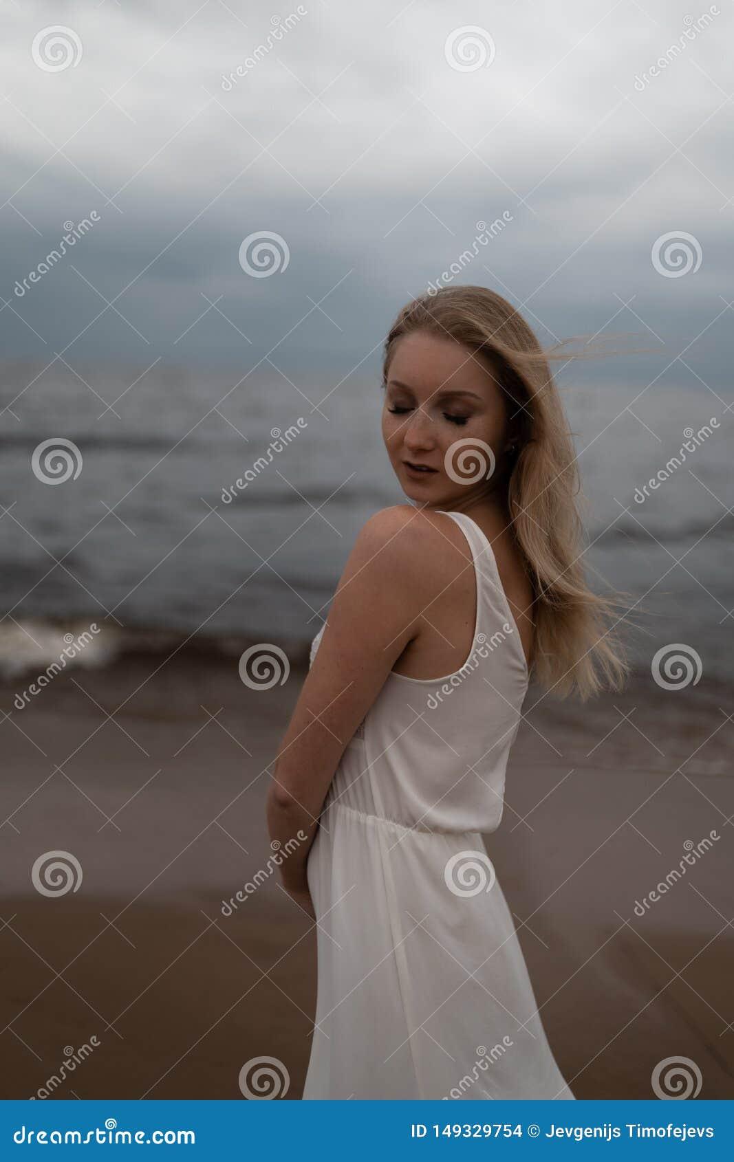 Retrato ascendente pr?ximo da ninfa loura nova bonita da praia da mulher no vestido branco perto do mar com ondas durante um somb