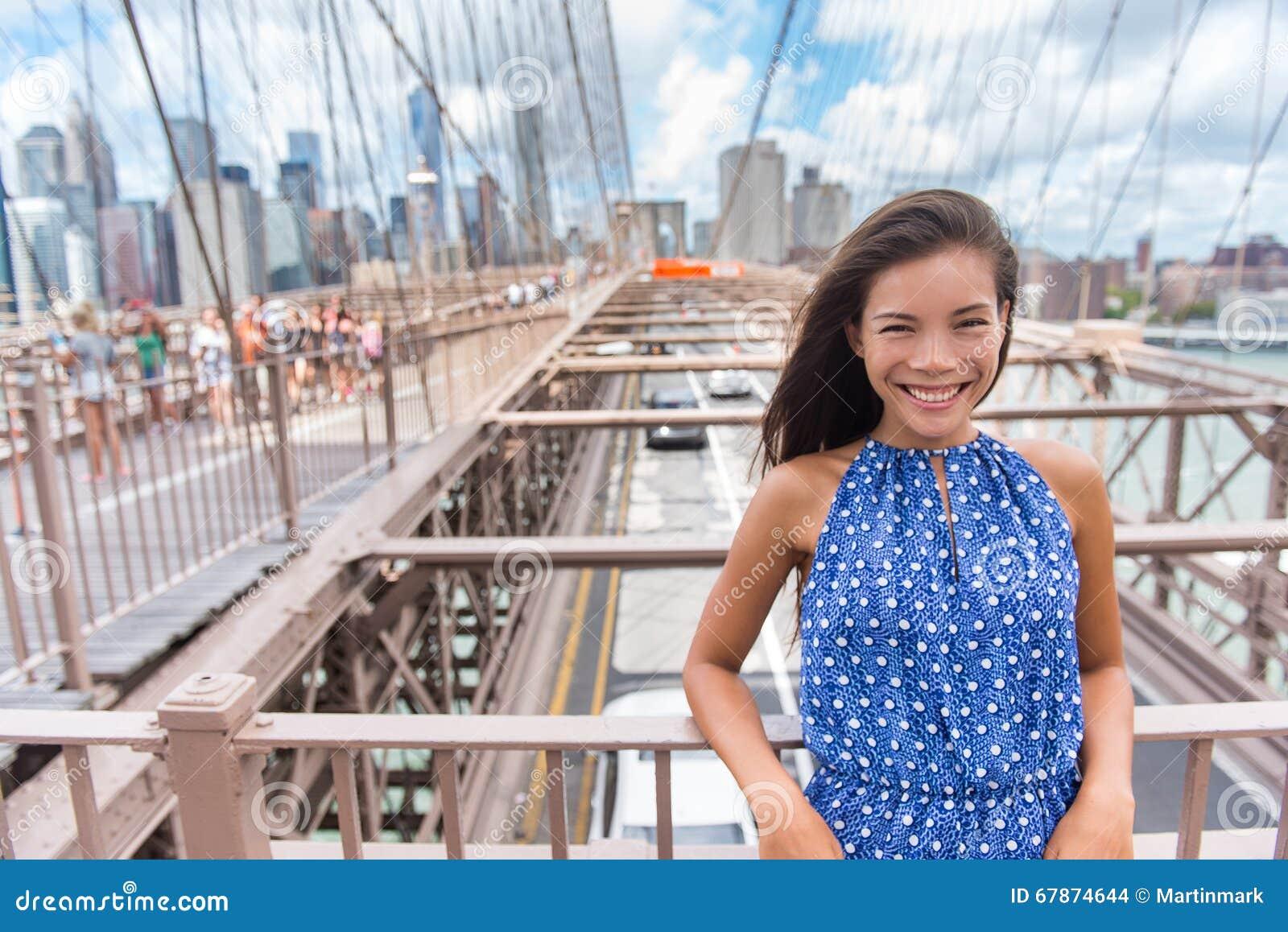 Retrato asiático joven hermoso de la mujer en el puente de Brooklyn, New York City