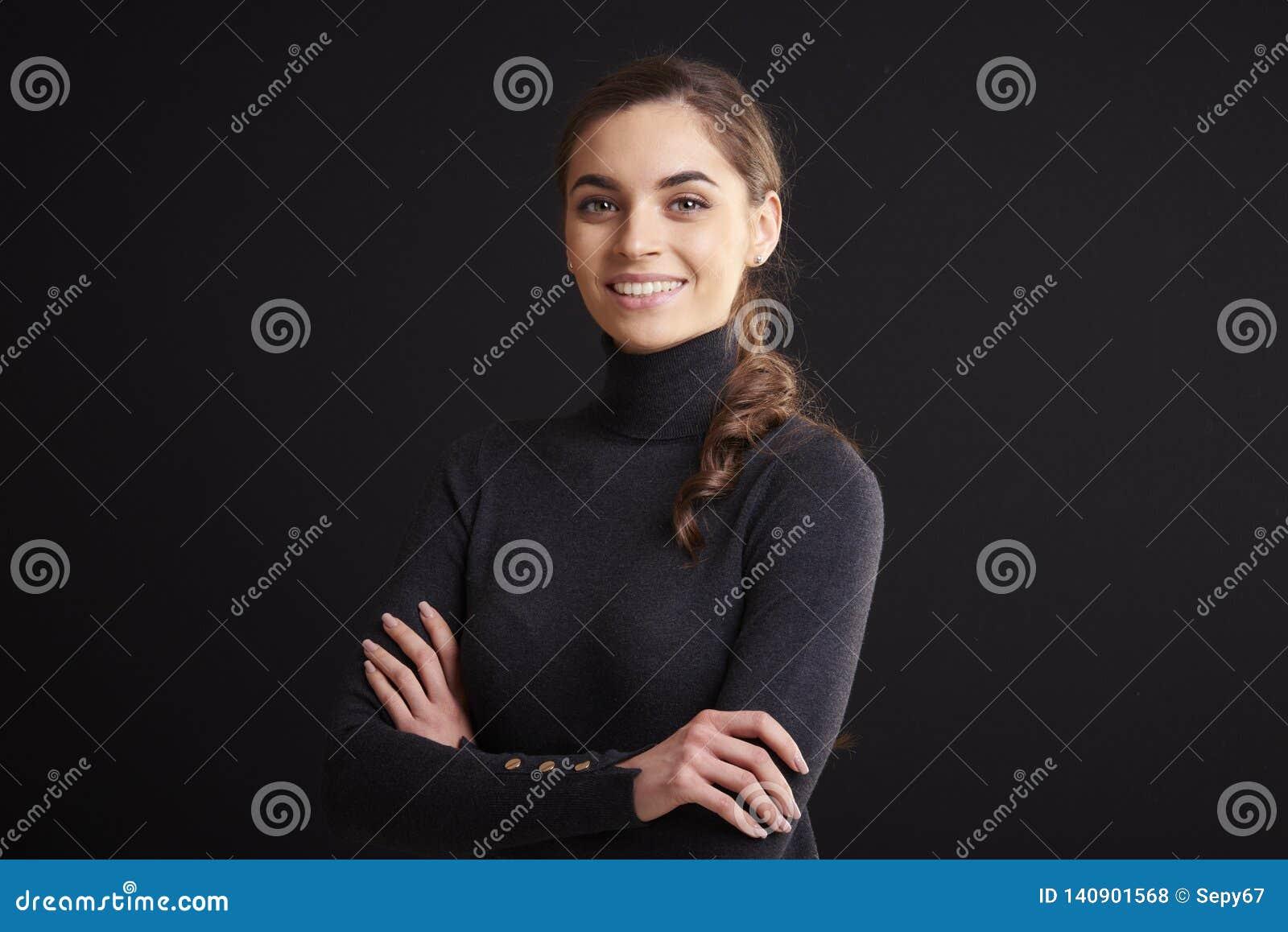 Retrato atractivo del estudio de la mujer joven mientras que se coloca en el fondo oscuro