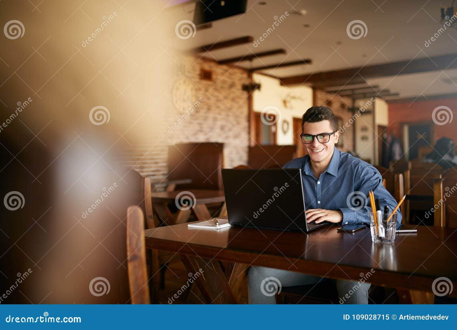Retrato auténtico del hombre de negocios sonriente joven que mira la cámara con el ordenador portátil en café El inconformista le