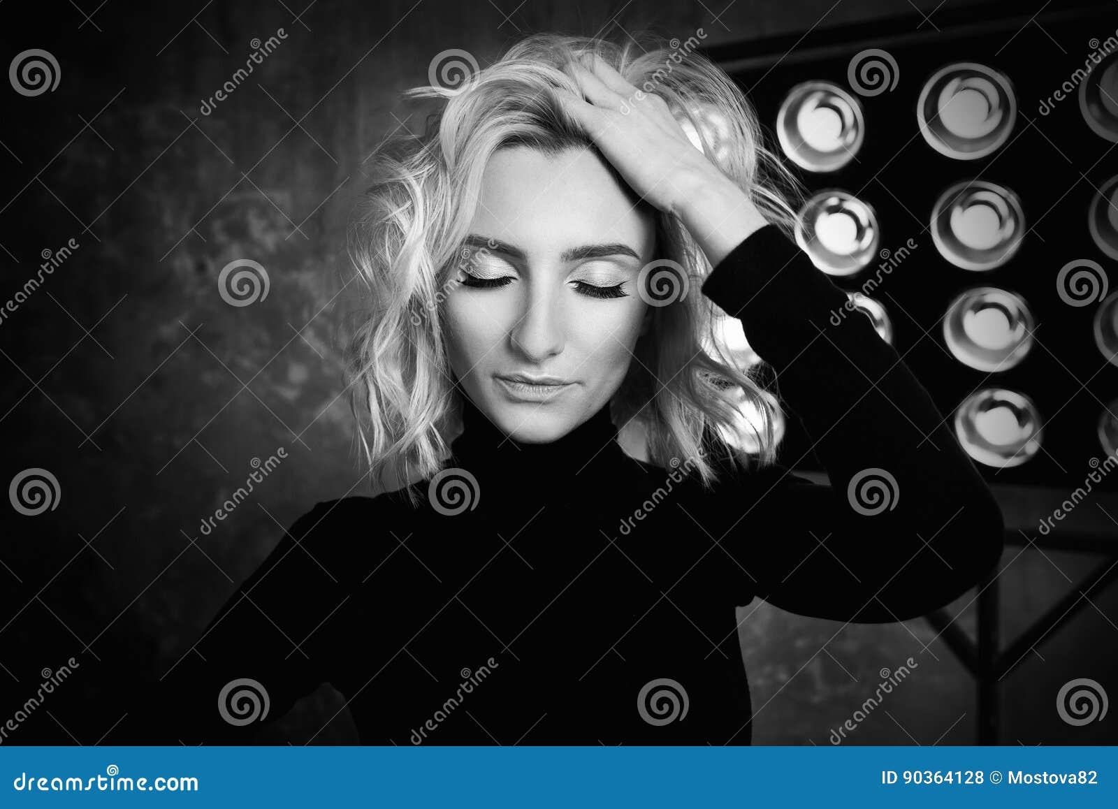 Retrato blanco y negro de la muchacha rizada atractiva hermosa elegante joven en suéter negro en la etapa