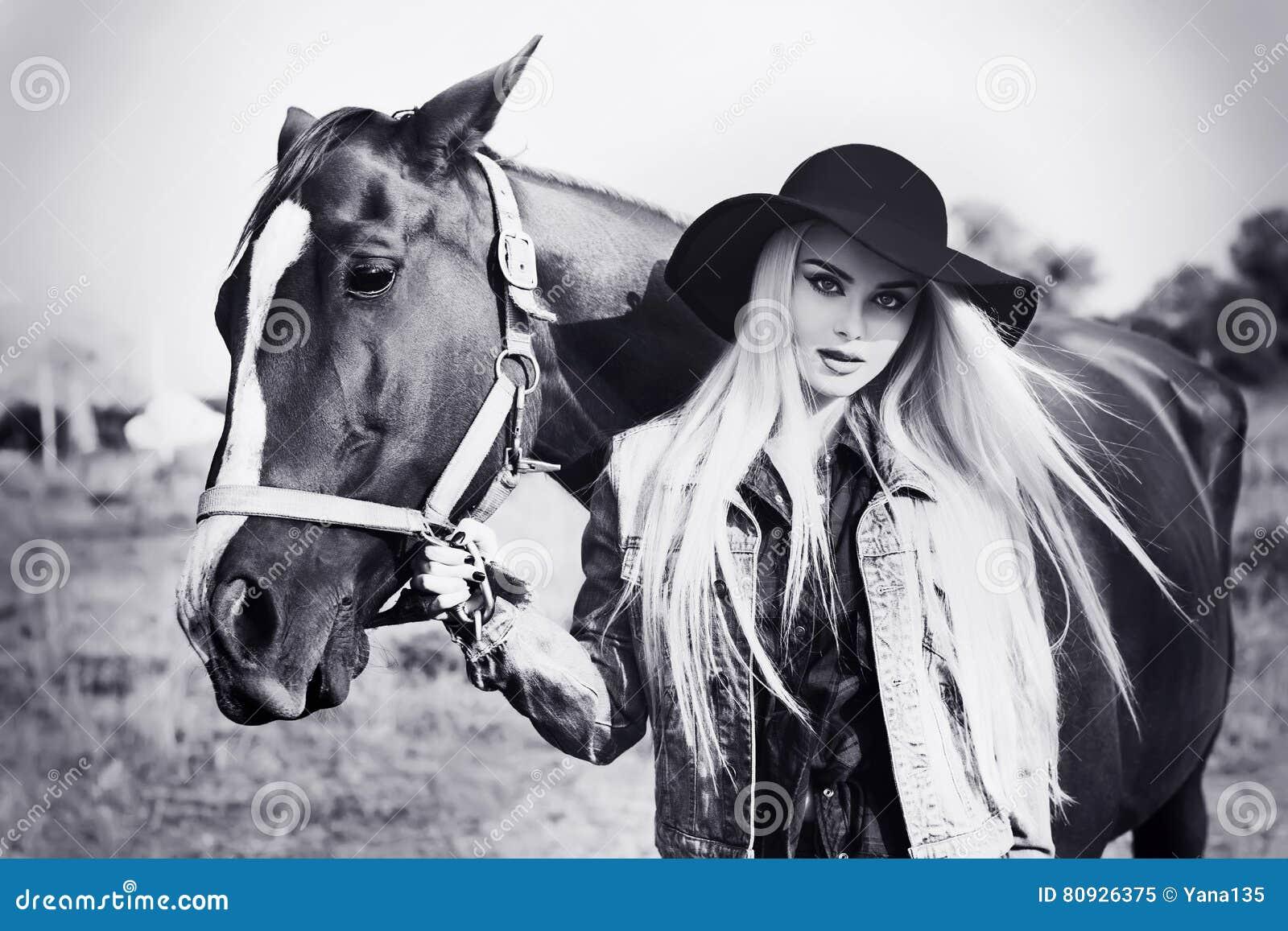 Retrato blanco y negro del vintage de una muchacha caucásica hermosa joven que sostiene un caballo