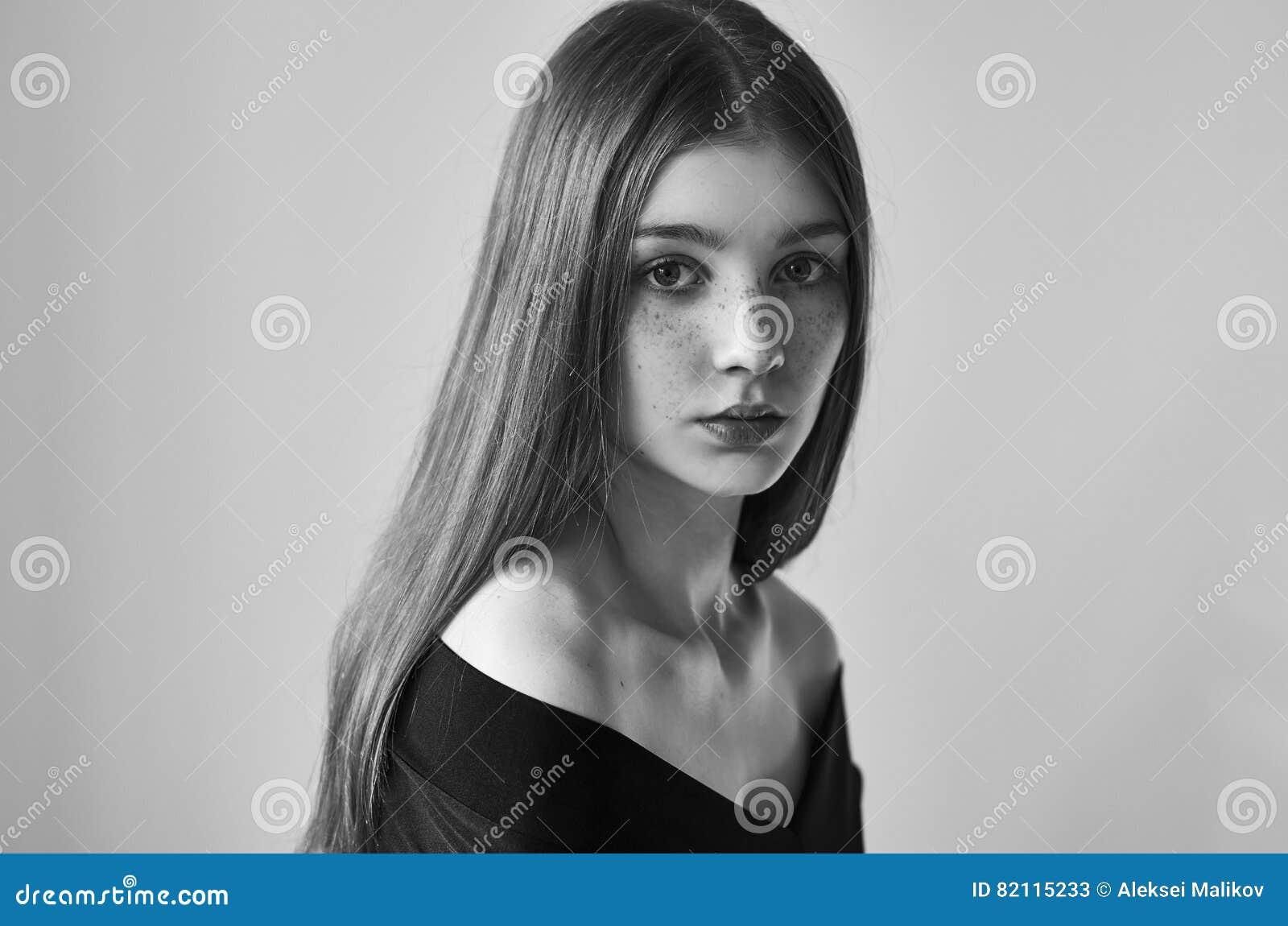Retrato blanco y negro dramático de una muchacha sola hermosa con las pecas aisladas en un fondo blanco en tiro del estudio