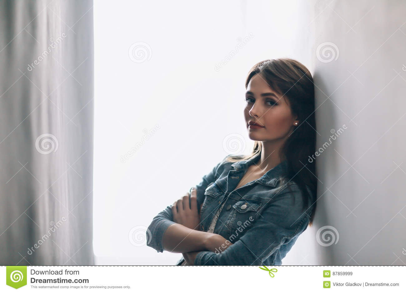 Retrato bonito da jovem mulher com braços cruzados