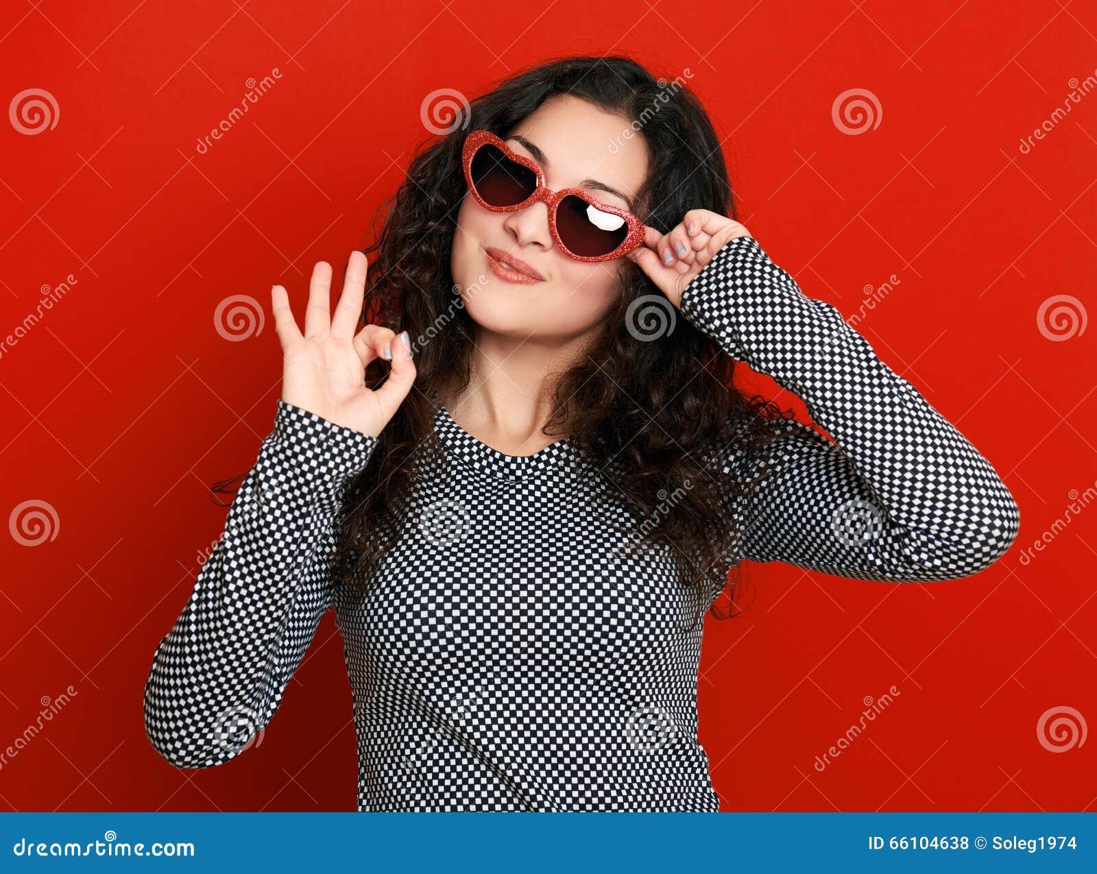 Retrato bonito do encanto da menina no vermelho em óculos de sol da forma do coração, cabelo encaracolado longo