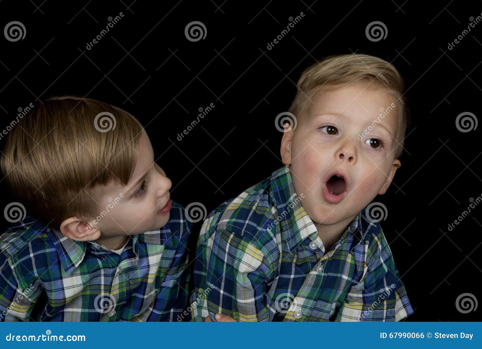 Retrato cândido de dois meninos novos que vestem camisas de harmonização