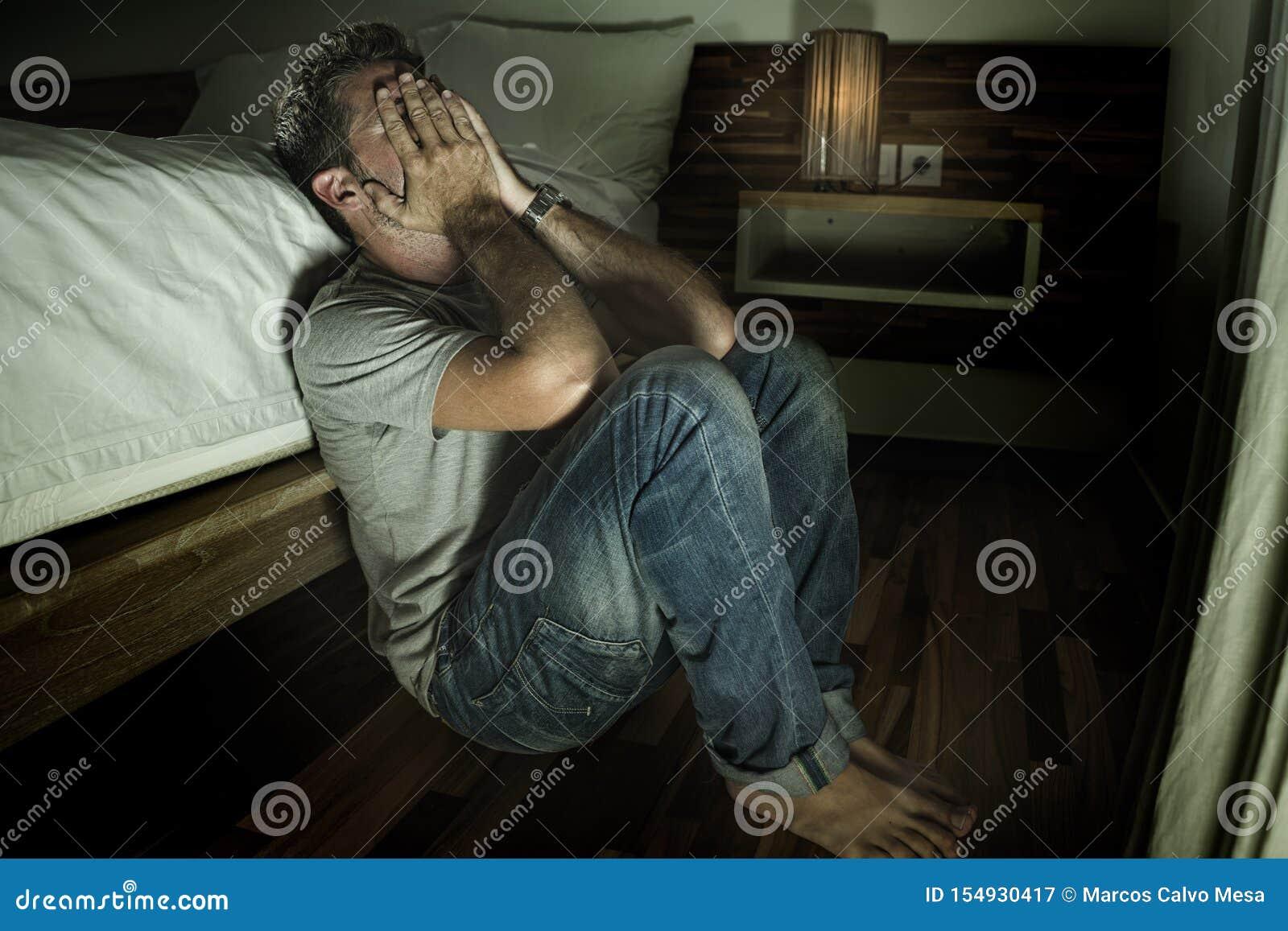 Retrato casero dramático del hombre solo desesperado y deprimido joven que se sienta en crisis sufridora enferma gritadora de la