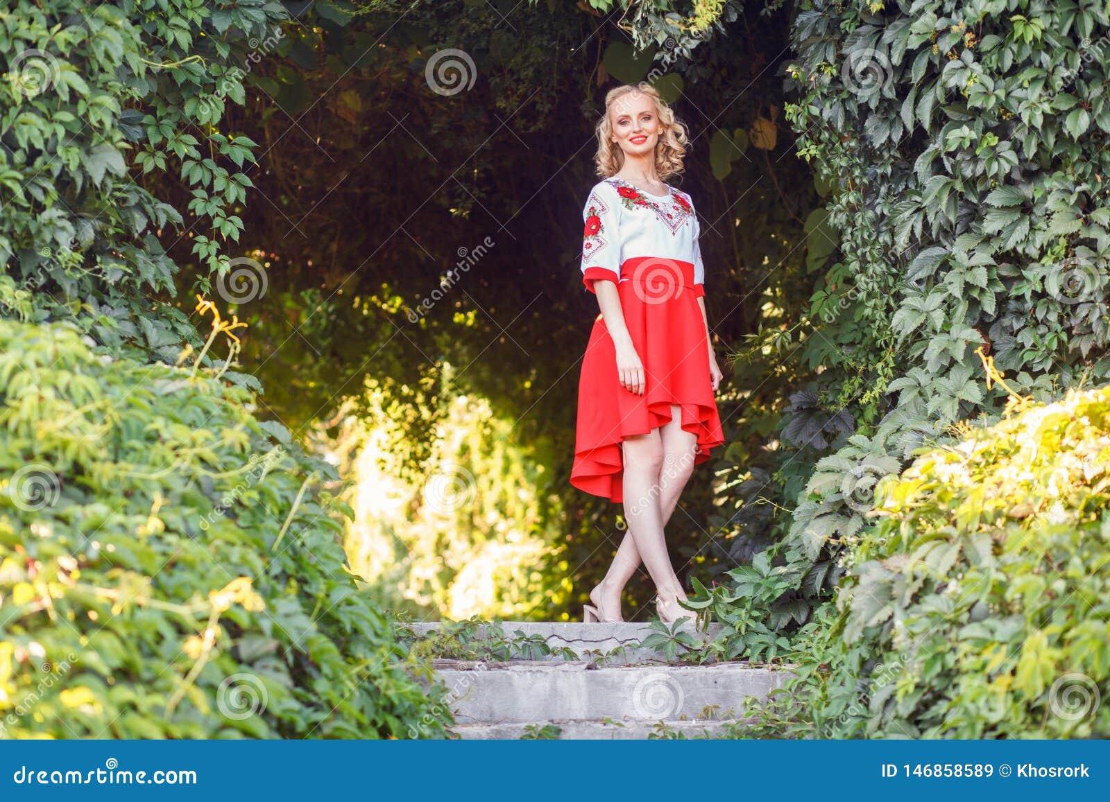 Retrato completo do comprimento da jovem mulher loura atrativa no vestido à moda que levanta perto do arco floral no jardim estar