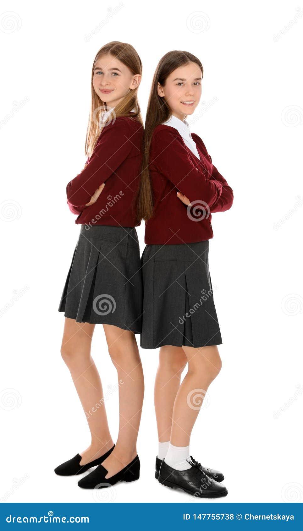 Retrato completo do comprimento dos adolescentes na farda da escola no branco