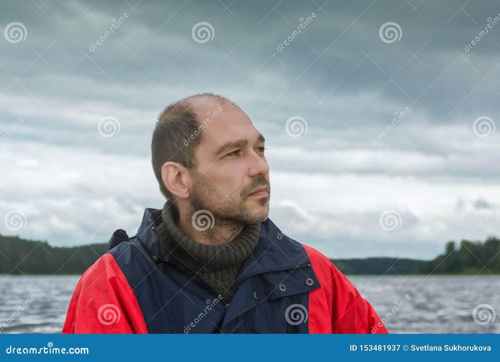 Retrato conceptual de un hombre barbudo pensativo contra un cielo cubierto
