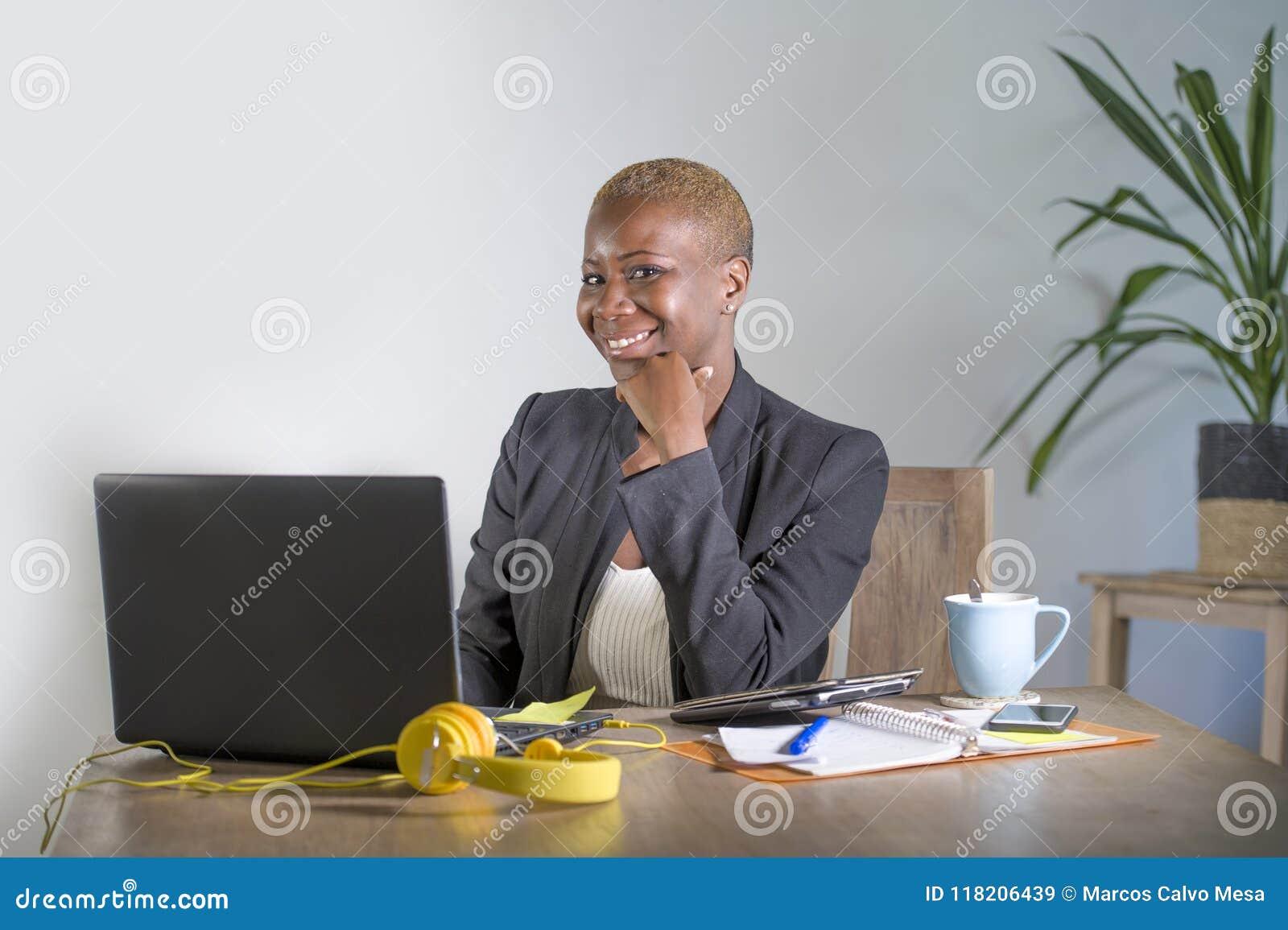 Retrato corporativo de la mujer de negocios afroamericana negra feliz y acertada joven que trabaja en el havi alegre sonriente de