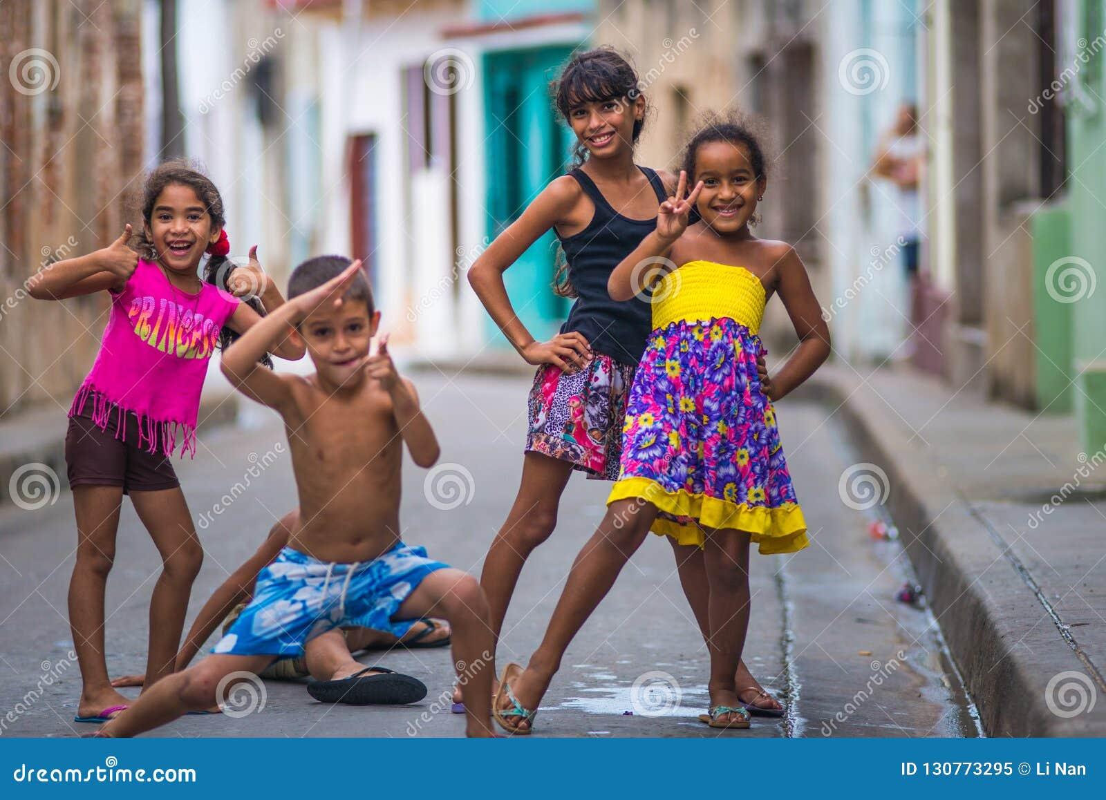 Retrato cubano feliz de la captura de la muchacha en callejón colonial colorido pobre con la cara de la sonrisa, en ciudad vieja,