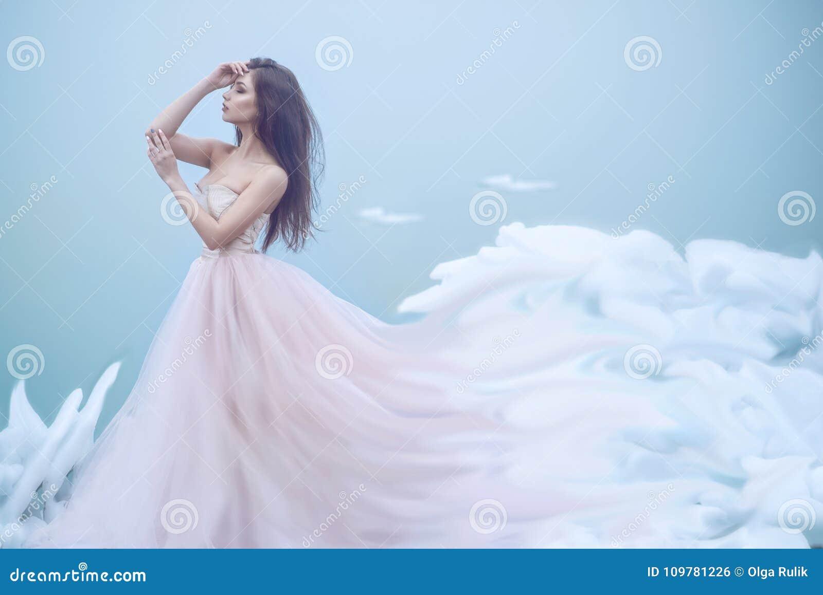 Retrato da arte de uma ninfa nova bonita no vestido de bola sem alças luxuoso que cresce em nuvens macias