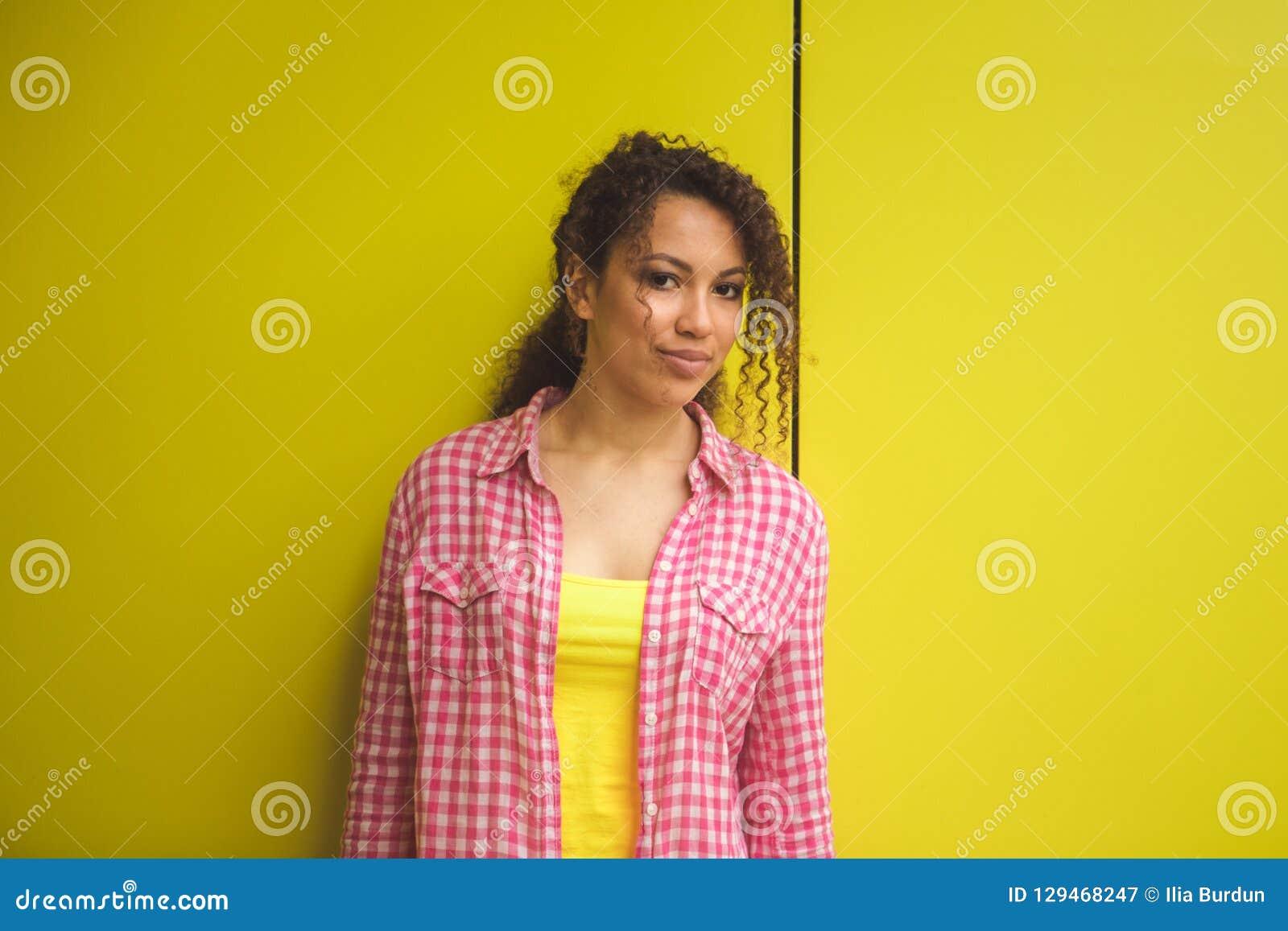 Retrato da beleza da menina afro-americano nova com penteado afro Menina que levanta no fundo amarelo, olhando a câmera
