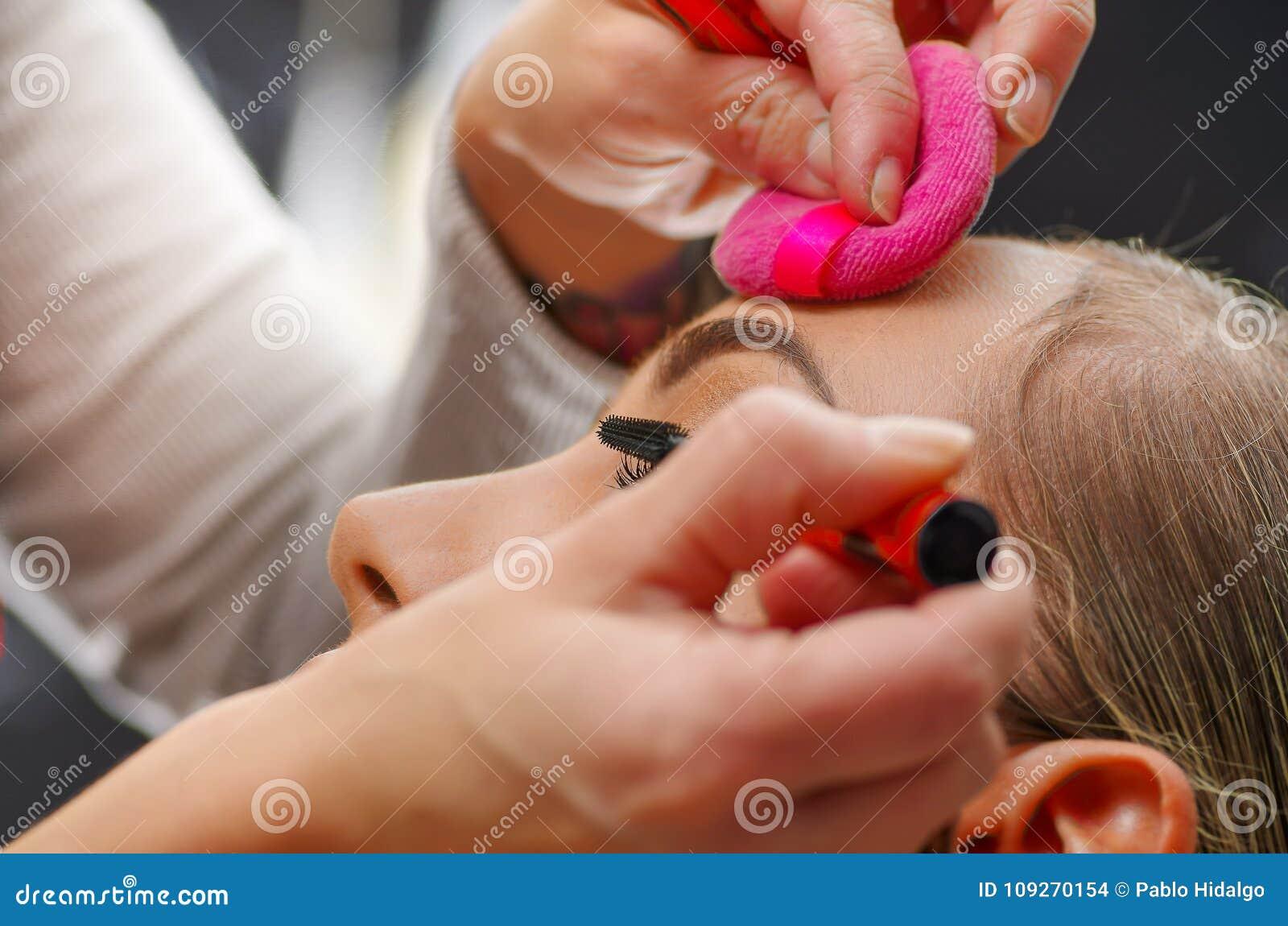 Retrato da cara bonita da jovem mulher que obtém a composição O artista está aplicando o rímel do olho em seus olhos A senhora