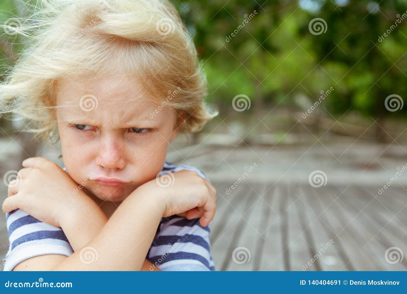 Retrato da cara da criança caucasiano irritada, infeliz com braços cruzados