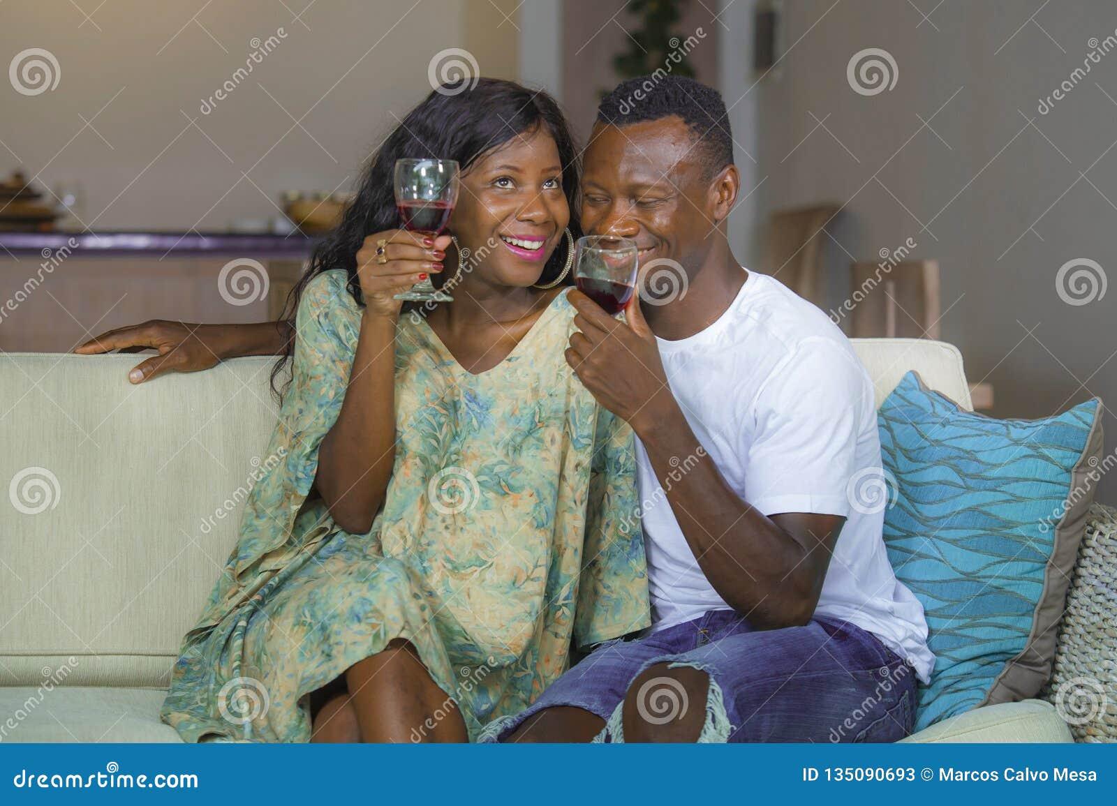 Retrato da casa do estilo de vida de pares afro-americanos pretos românticos e felizes novos no copo bebendo do vinho do amor no