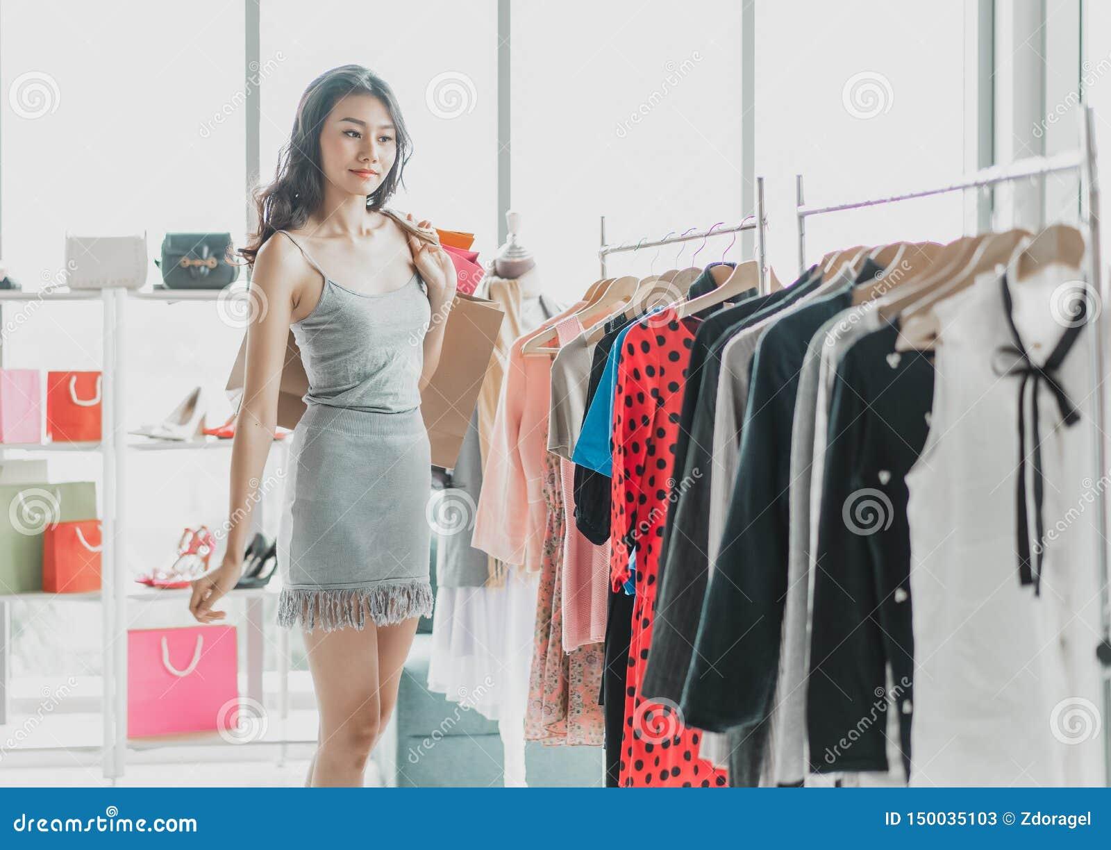 Retrato da compra asiática nova da mulher para alguma roupa em uma loja compra, forma, estilo e conceito dos povos