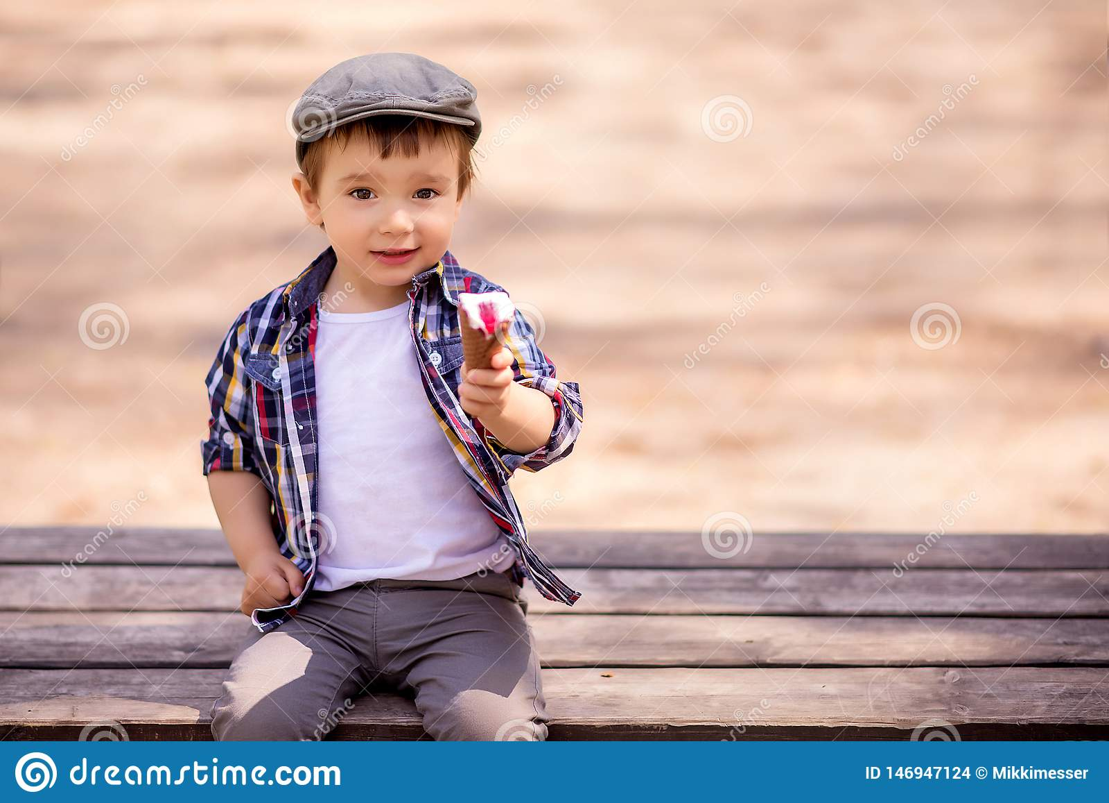 Retrato da criança extravagante da criança que senta-se no banco exterior e que guarda um gelado que oferece compartilhar da sobr