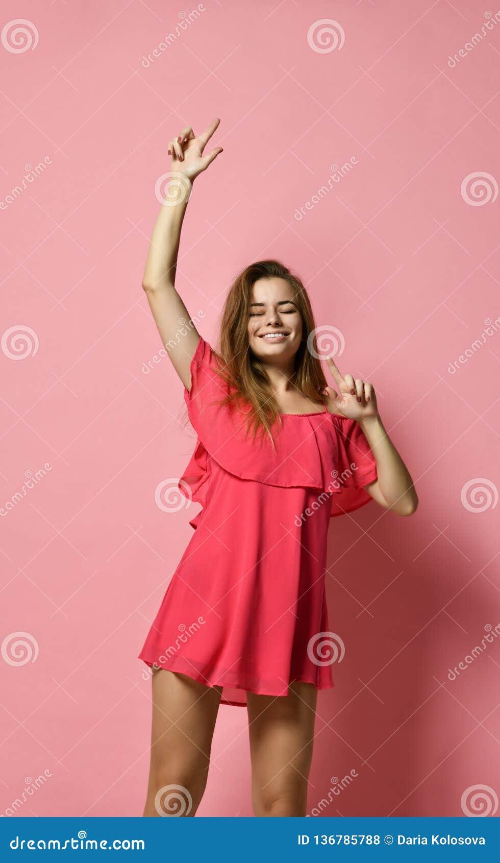 Retrato da dança caucasiano moreno da menina contra a parede cor-de-rosa com sorriso, bom humor de júbilo