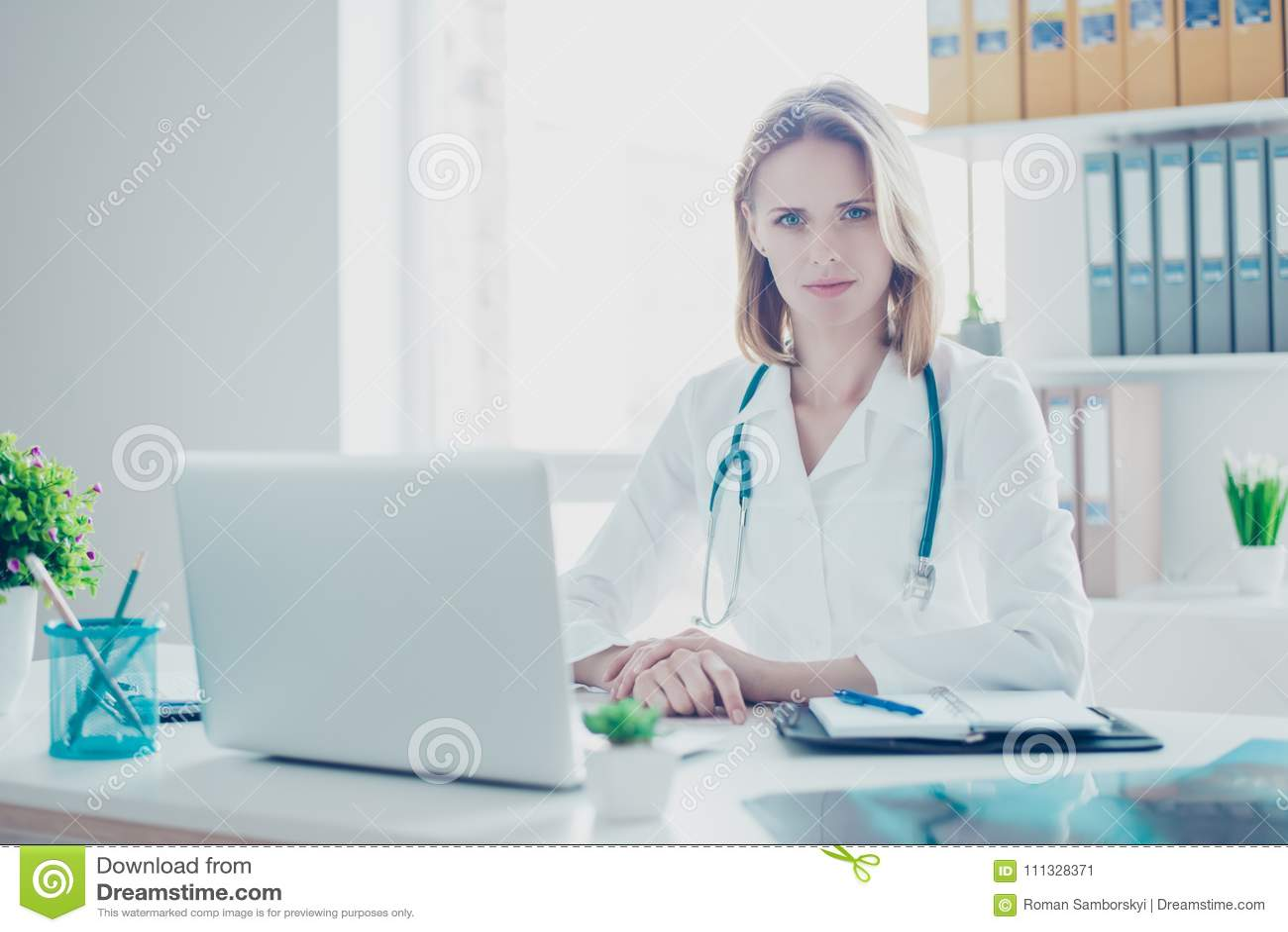 Retrato da estudante de medicina concentrada segura que veste o revestimento branco, sh