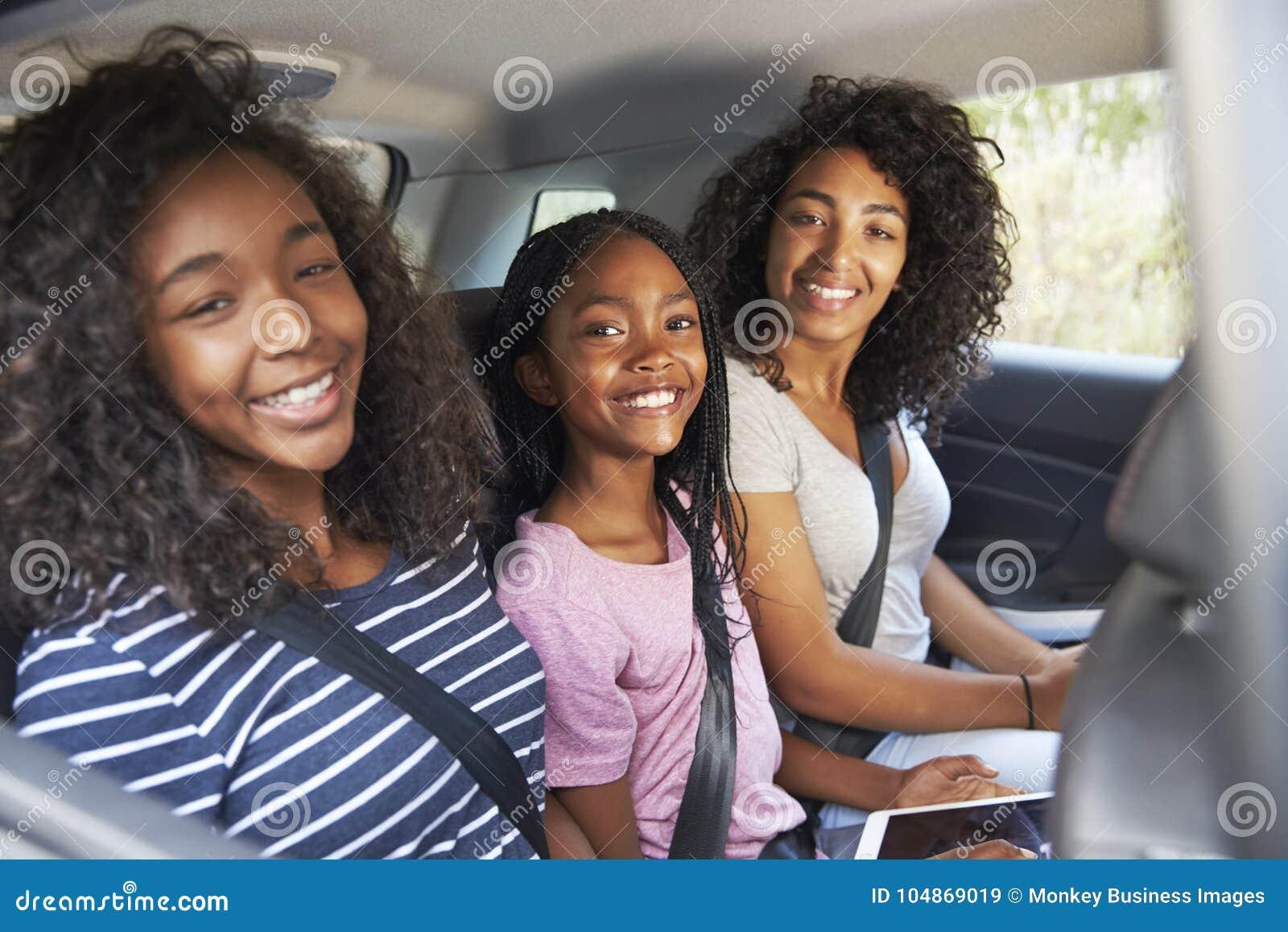 Retrato da família com as crianças adolescentes no carro na viagem por estrada