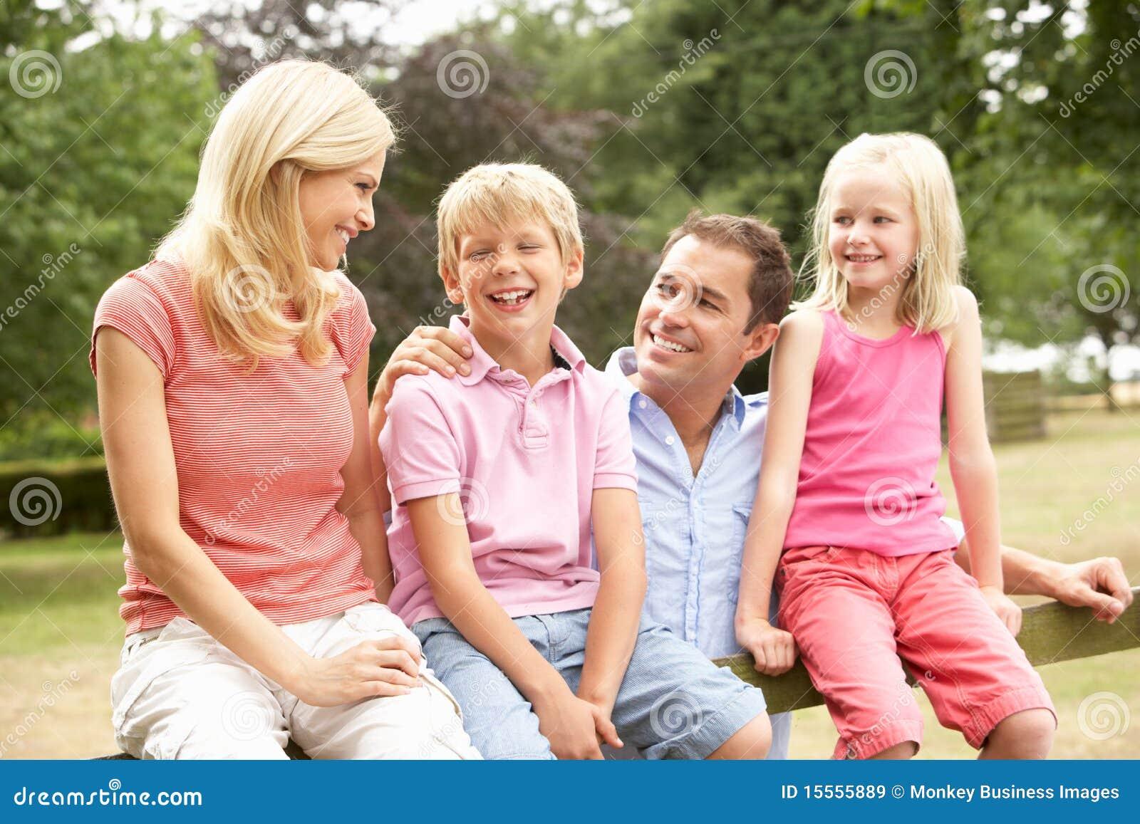 Retrato da família que senta-se na cerca no campo