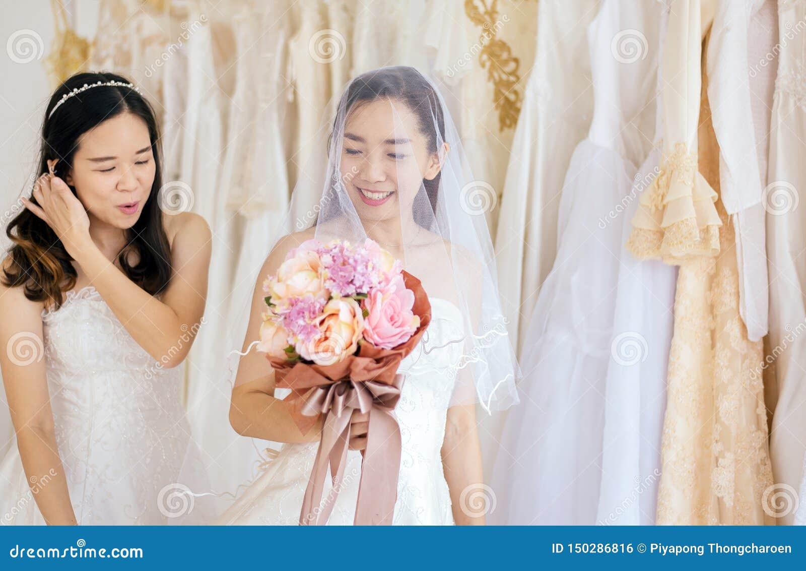Retrato da felicidade asiática da noiva da mulher dos pares bonitos e togethe engraçado, cerimônia no dia do casamento, feliz e n
