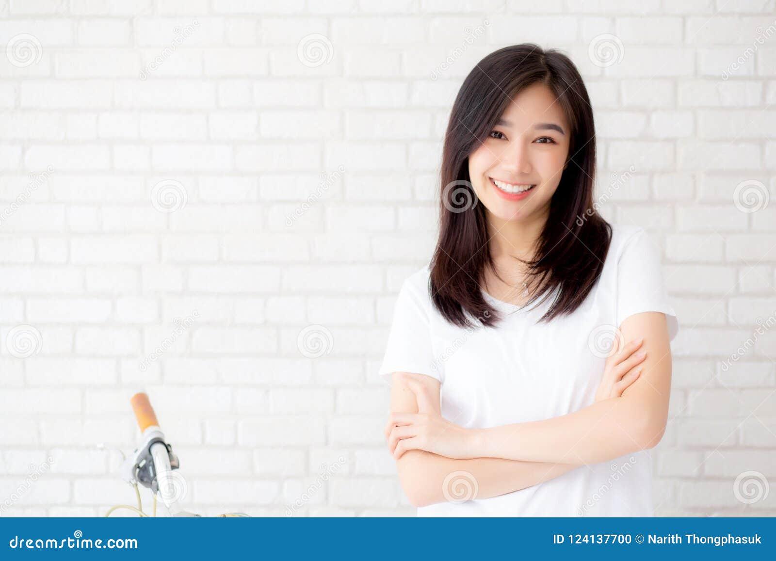 Retrato da felicidade asiática nova bonita da mulher que está no fundo cinzento do tijolo da parede do grunge da textura do cimen