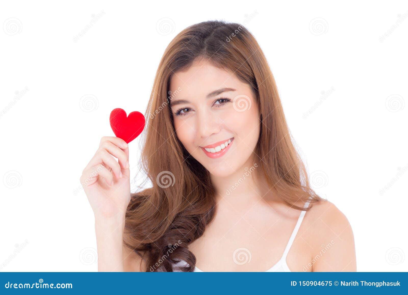 Retrato da jovem mulher asi?tica bonita que guarda o descanso vermelho e o sorriso da forma do cora??o isolado no fundo branco