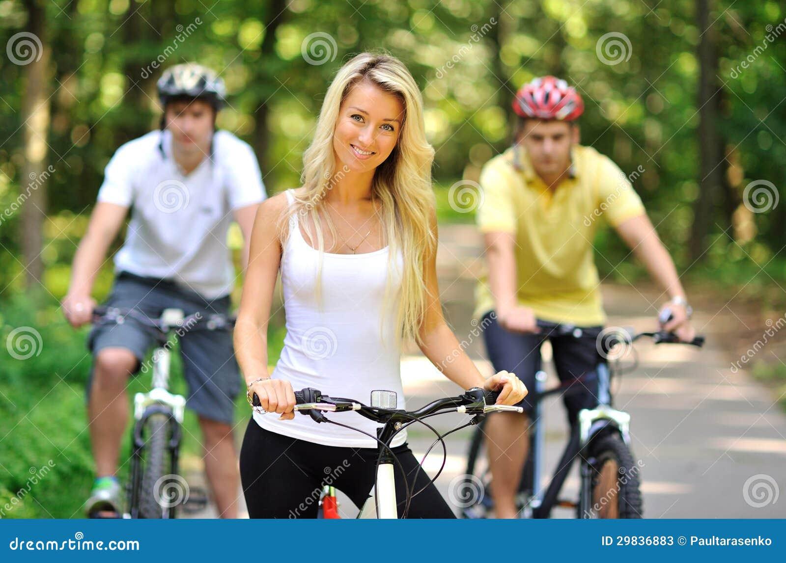 Retrato da jovem mulher atrativa na bicicleta e nos dois homens atrás