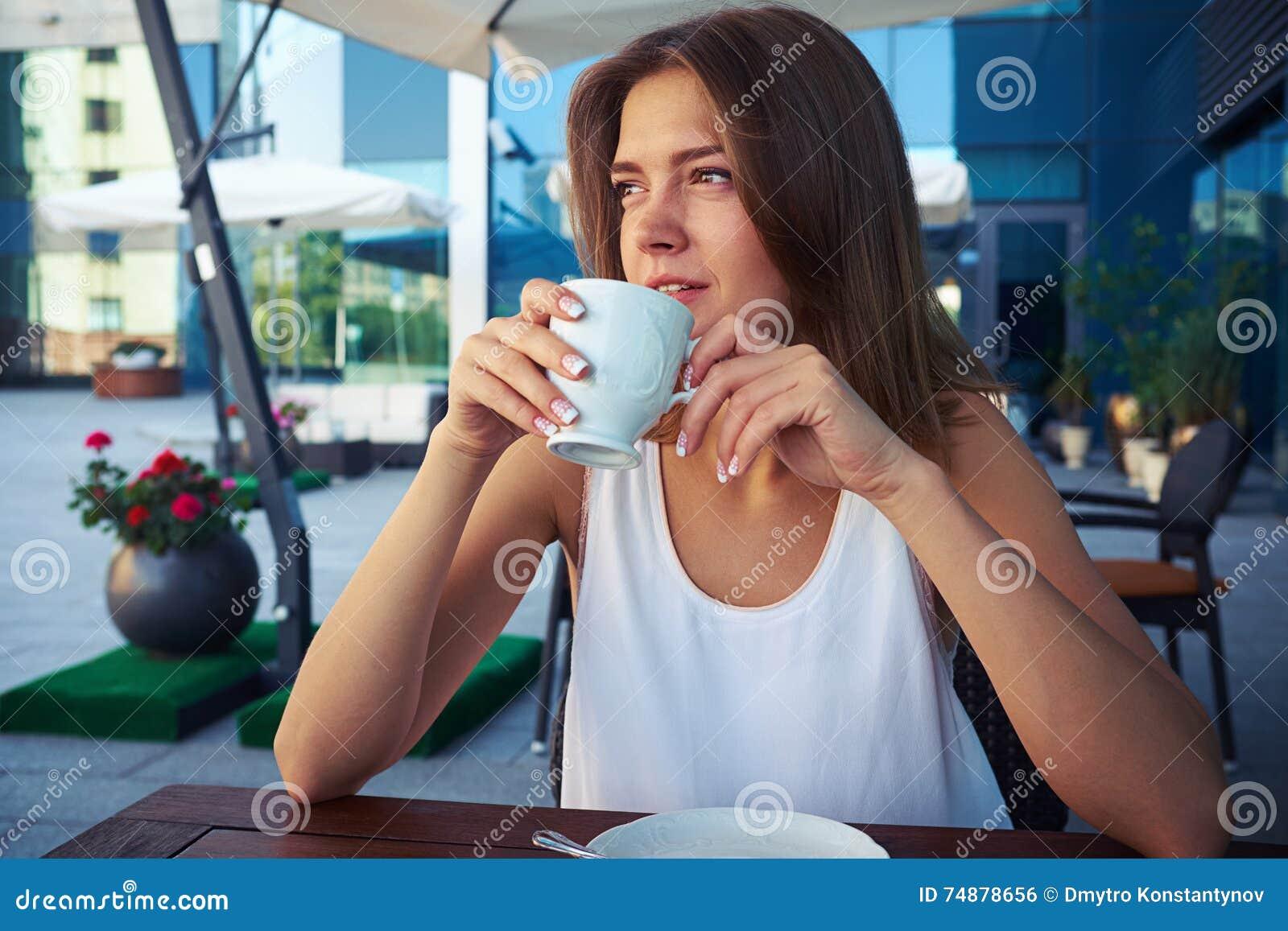 Retrato da jovem mulher bonita no coffe bebendo do café da rua