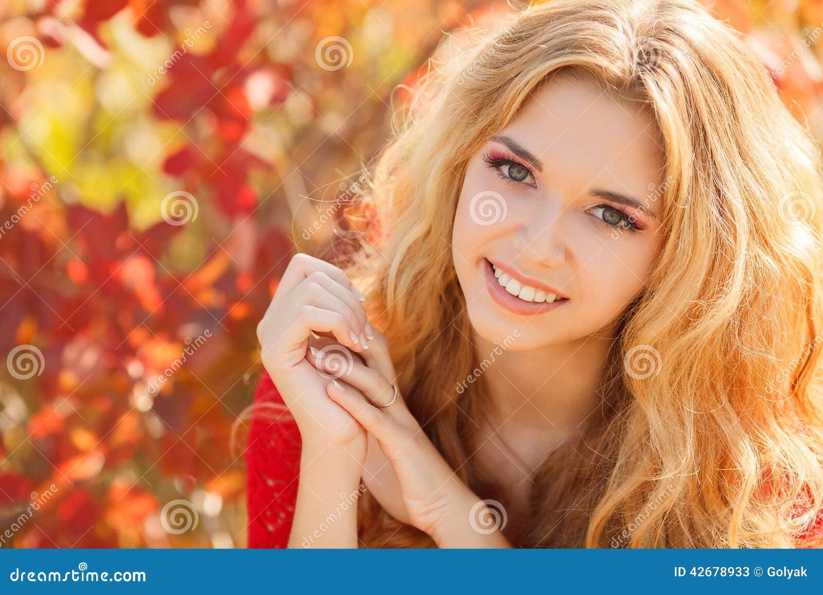 Retrato da jovem mulher bonita no parque do outono