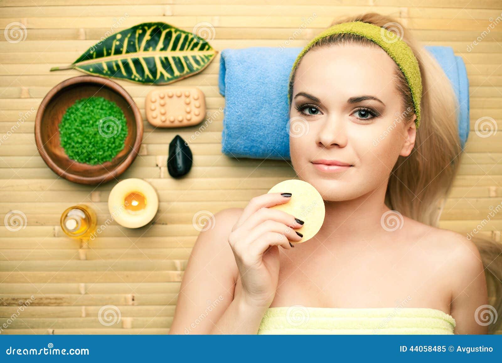 Retrato da jovem mulher bonita que toca em sua cara com esponja