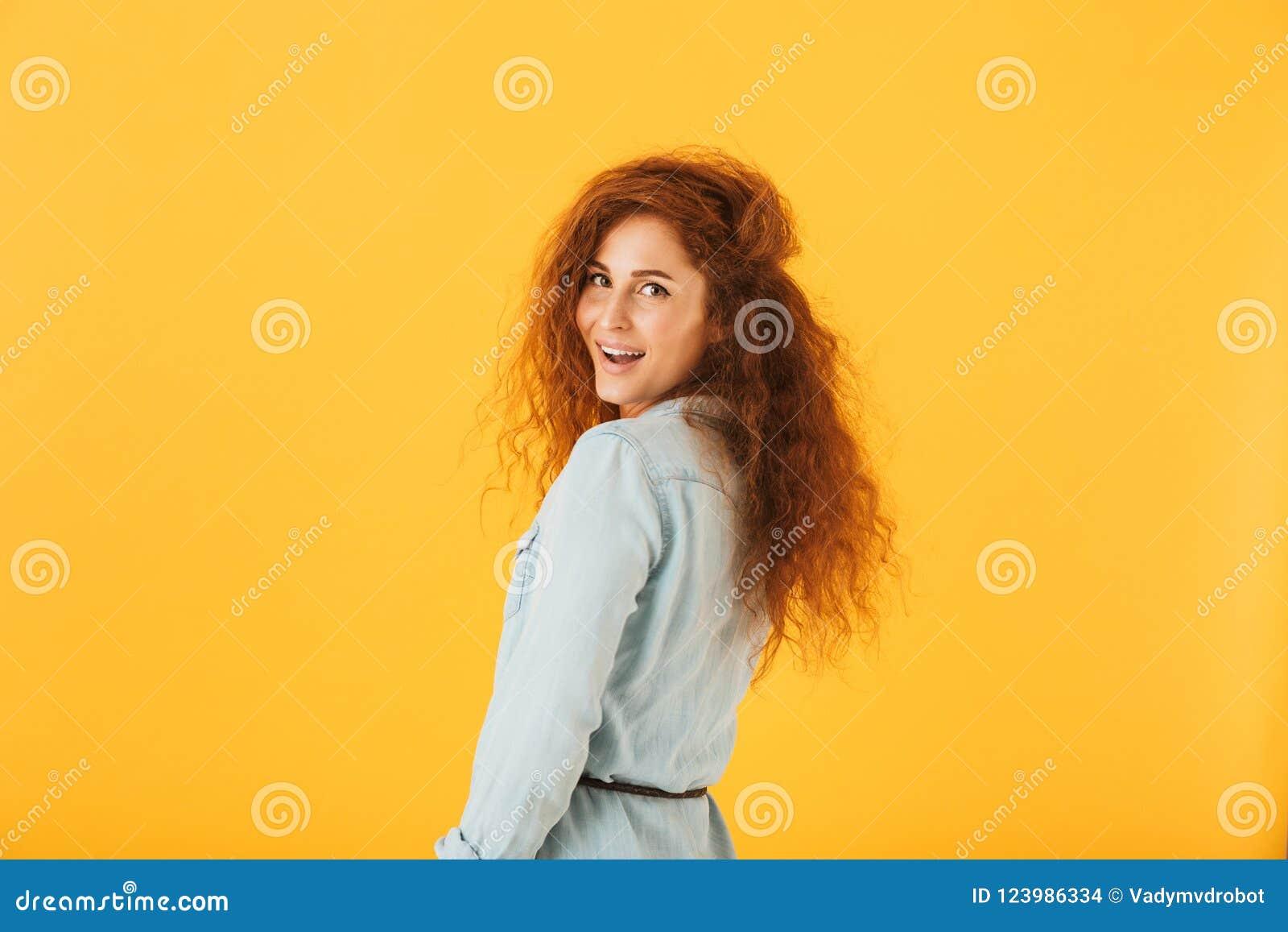 Retrato da jovem mulher bonita 20s com o cabelo encaracolado que sorri em