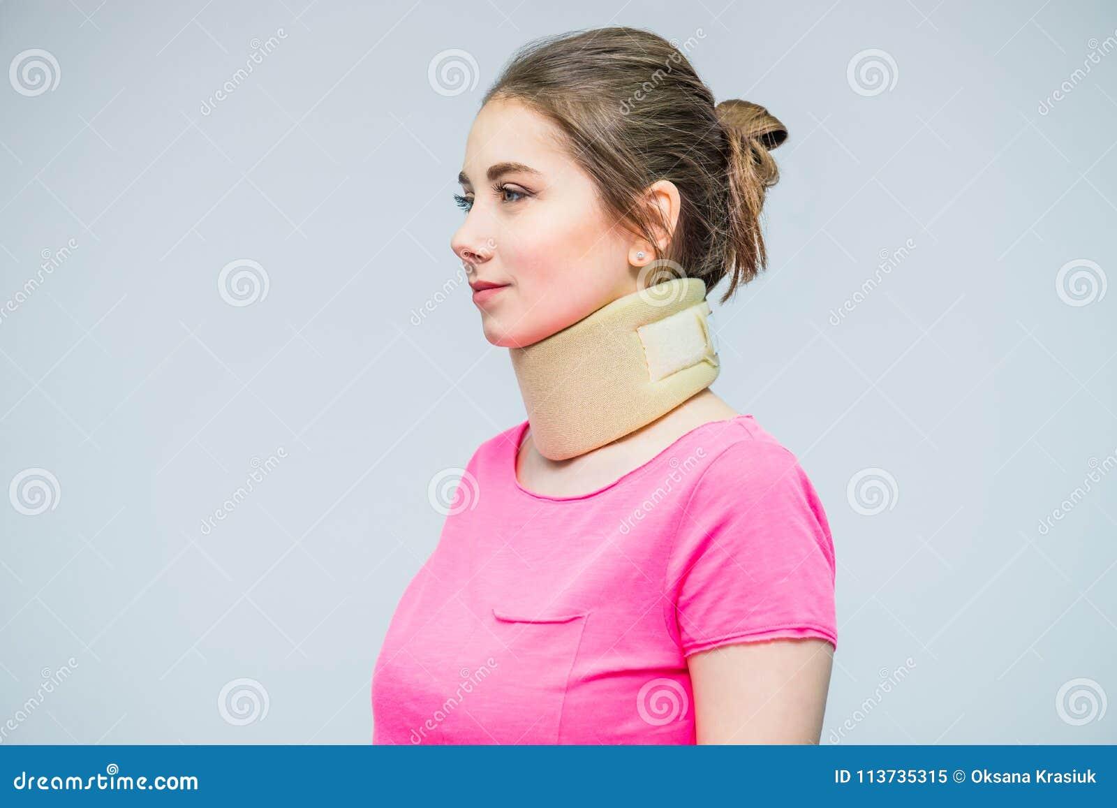 Retrato da jovem mulher com um ferimento do pescoço, um colar do osteochondrosis a impedir e uma fisioterapia Tratamento da dor N