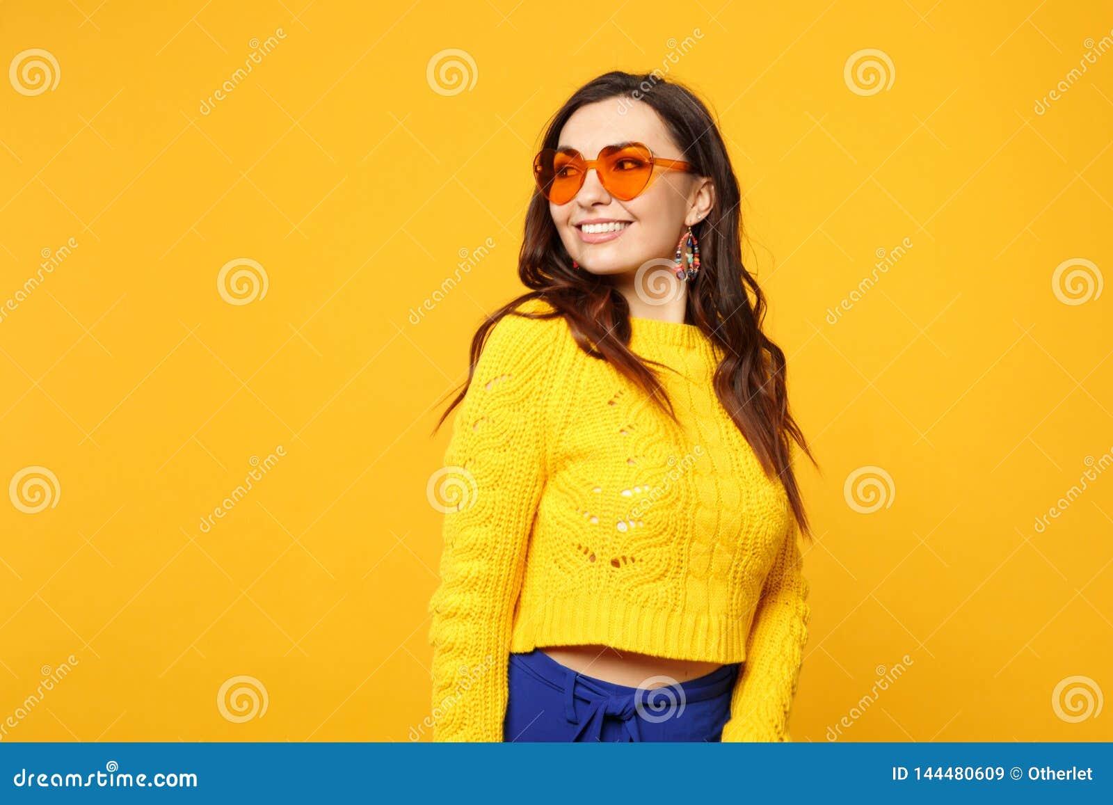 Retrato da jovem mulher de sorriso bonita na camiseta, calças azul, vidros do coração que olham isolados de lado na laranja amare