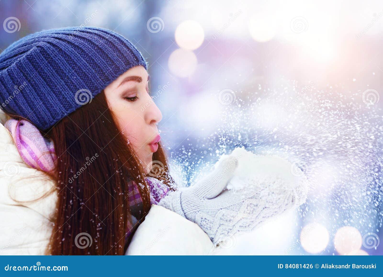 Retrato da jovem mulher do inverno Neve de sopro da menina do inverno Beleza Girl modelo adolescente alegre que tem o divertiment