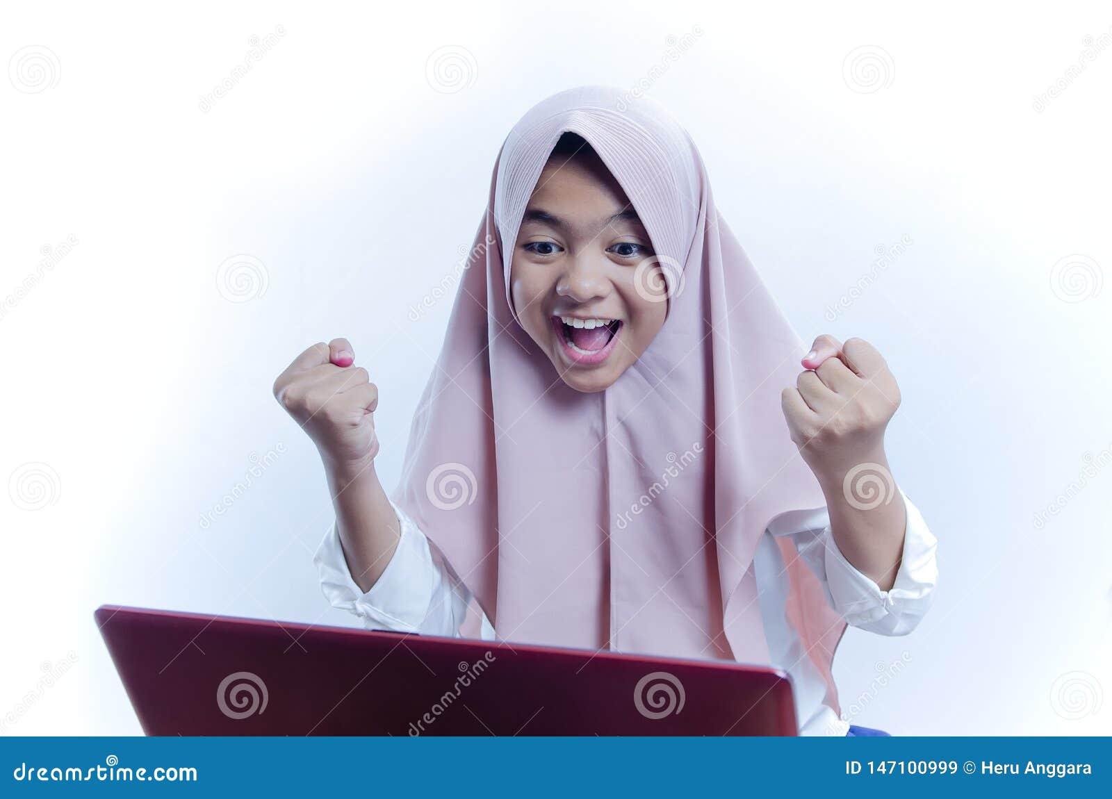 Retrato da jovem mulher feliz que comemora o sucesso com braços acima e grito para fora na frente do portátil
