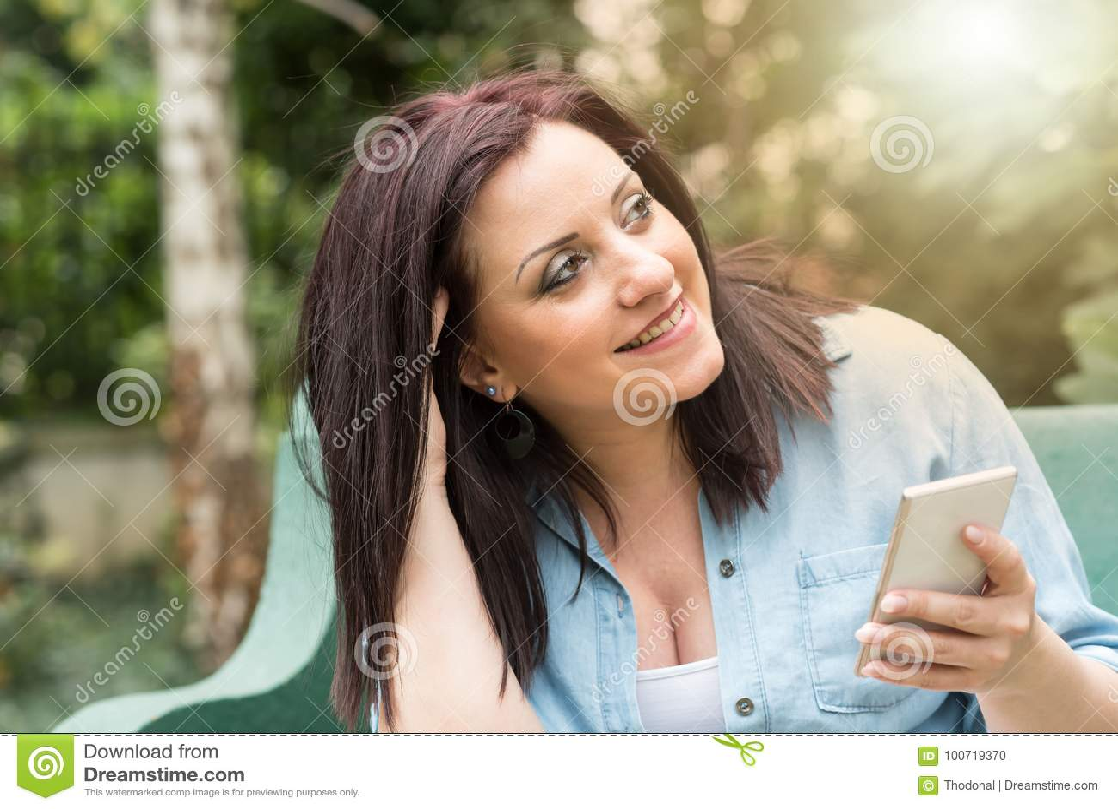 Retrato da jovem mulher feliz que usa seu telefone celular, efeito da luz