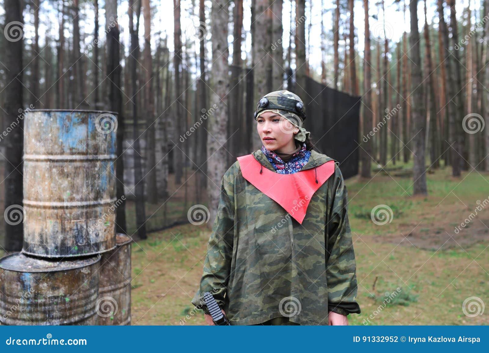 Retrato da jovem mulher na camuflagem com um rifle outdoors