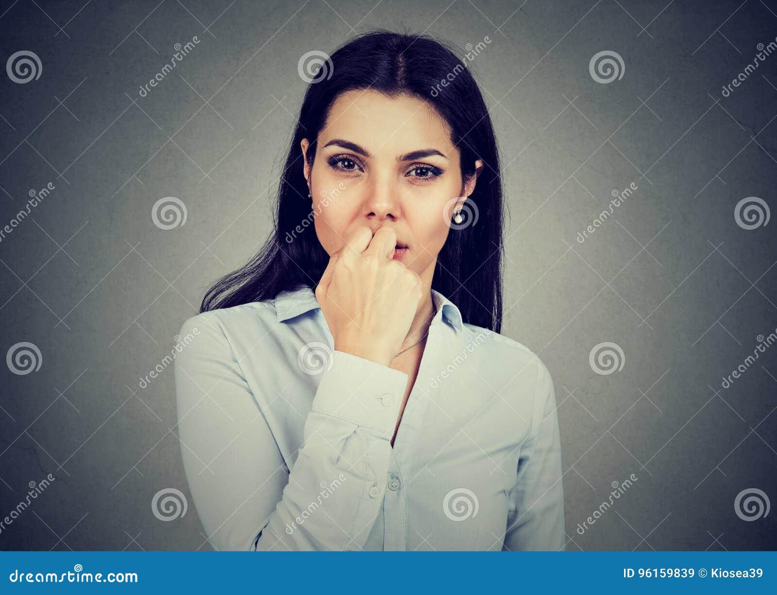 Retrato da jovem mulher preocupada que olha ansiosamente a câmera