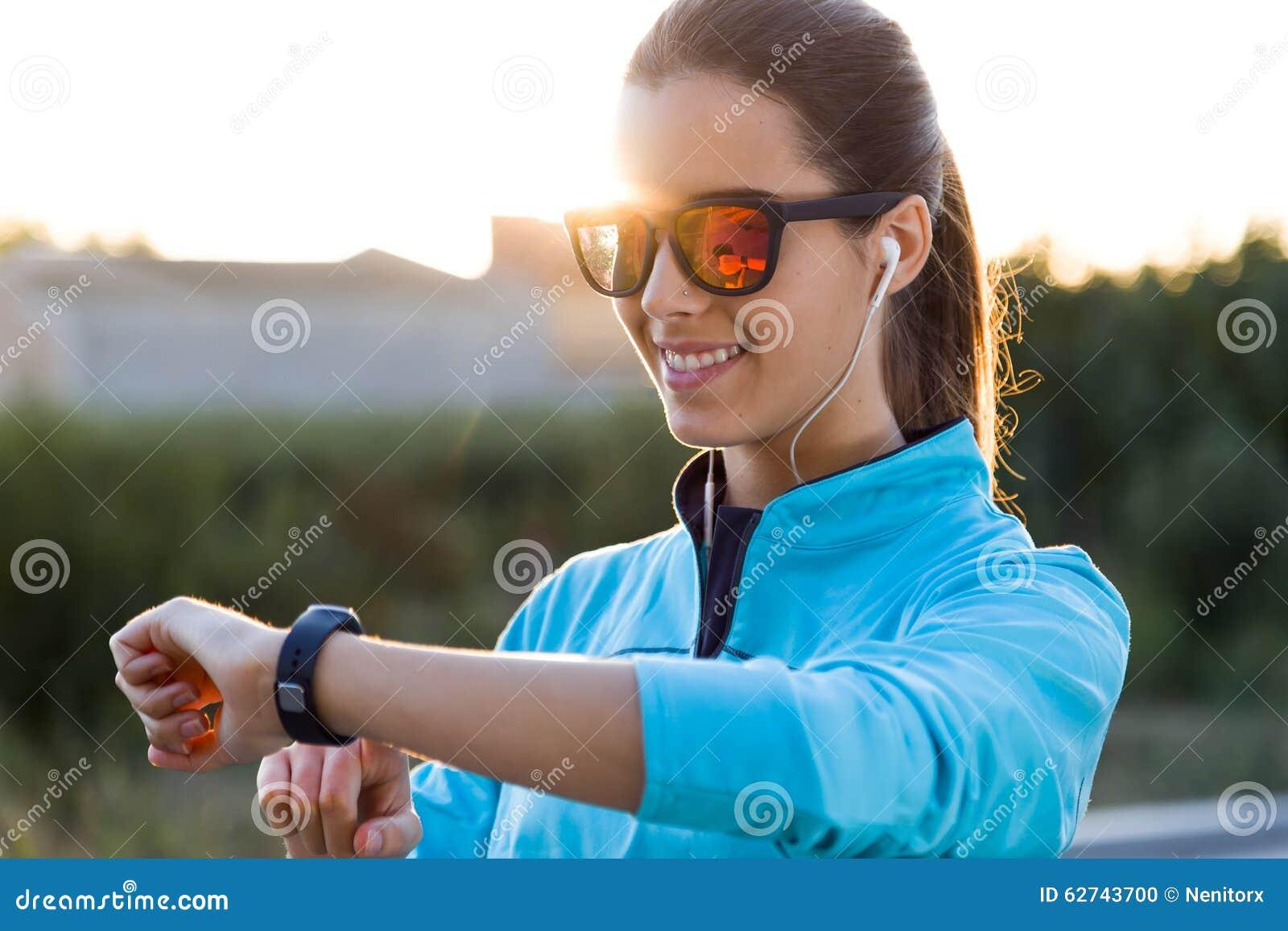 Retrato da jovem mulher que usa-se eles smartwatch após a corrida